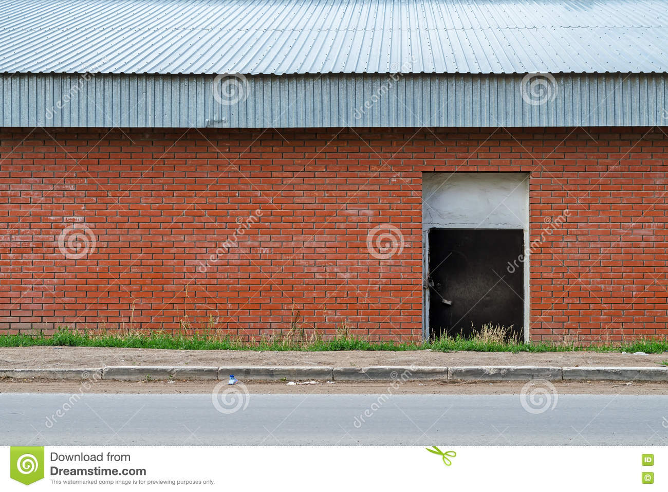 Facade Warehouse Near The Road Brick Wall With A Door And