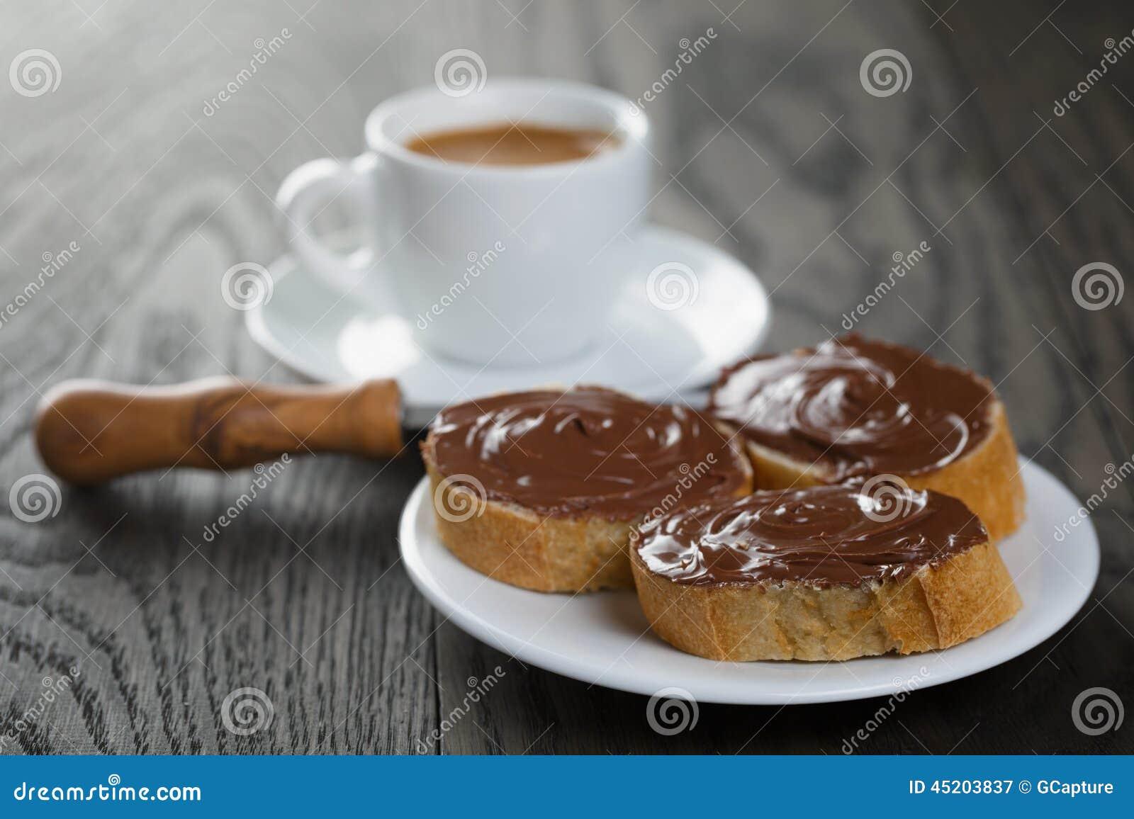 Faccia colazione con le fette delle baguette e del caffè espresso con la diffusione del cioccolato
