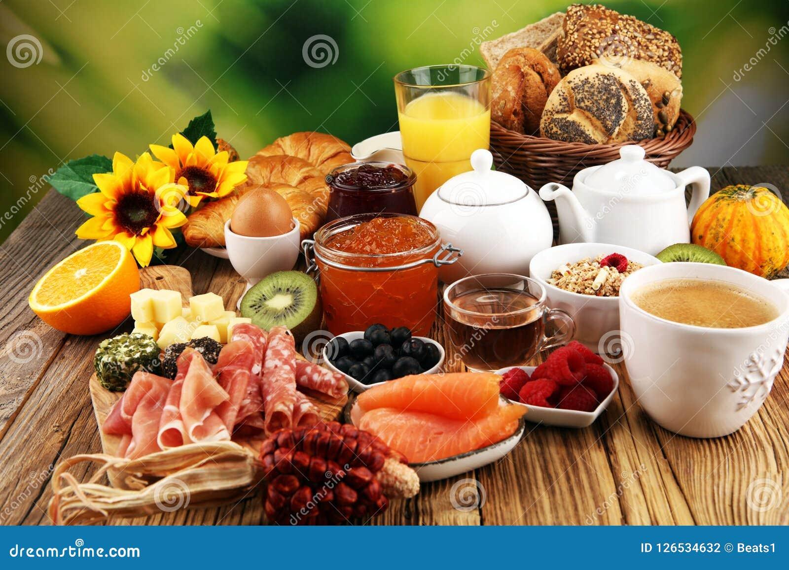 Faccia colazione sulla tavola con i panini, i croissant, il coffe ed il succo del pane