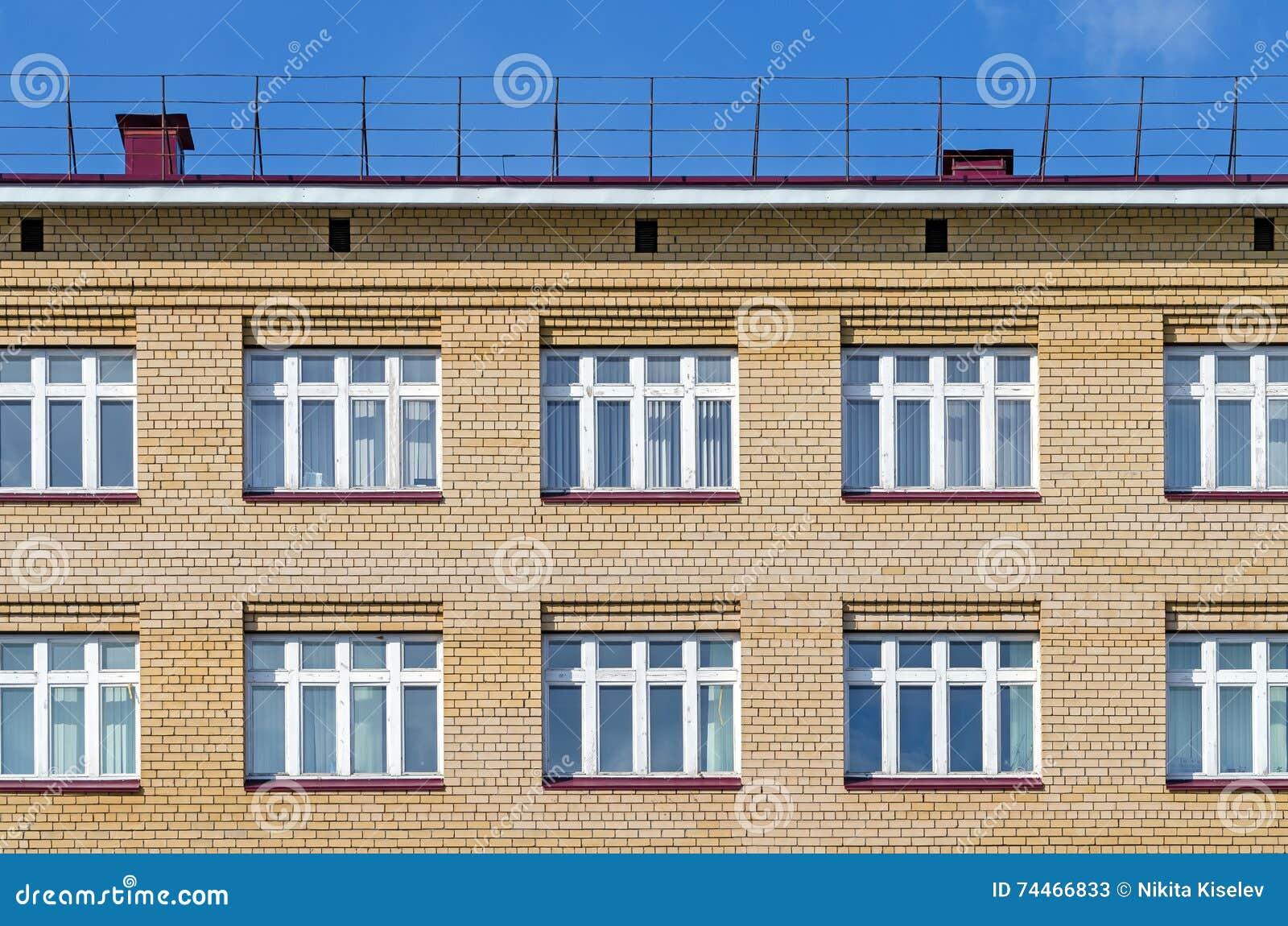 Facciata del mattone della casa con un tetto e le finestre - Finestre bianche ...