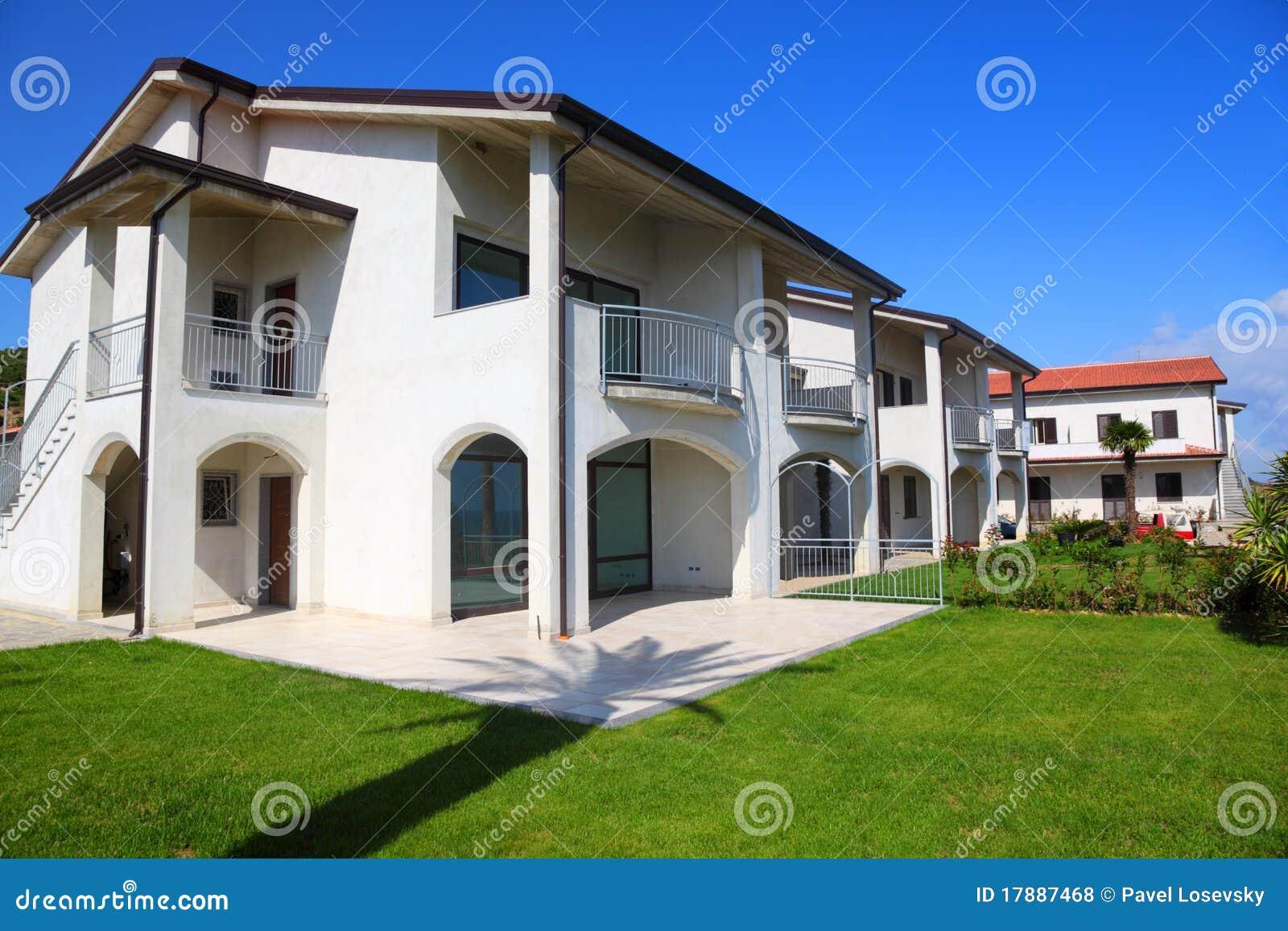 Facciata della casa a due piani bianca con il giardino for Piani casa com