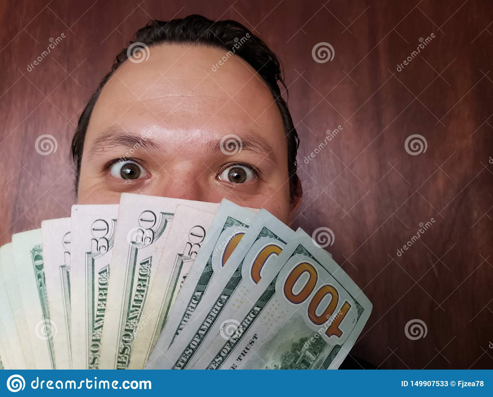 face with emotion expression of a young man and American banknotes