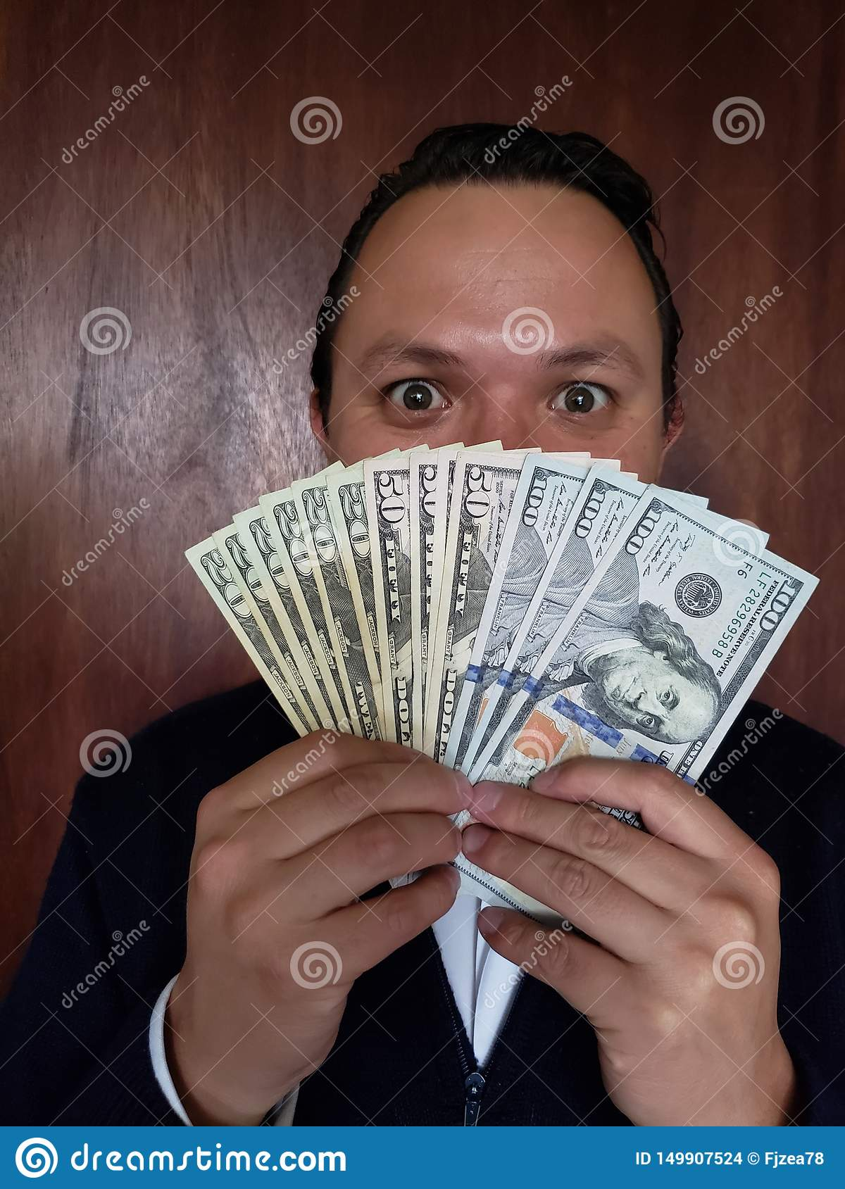 face with emotion expression of a young man and holding American banknotes