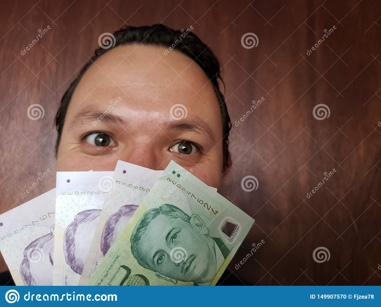 face with emotion expression of a young man and singaporean banknotes