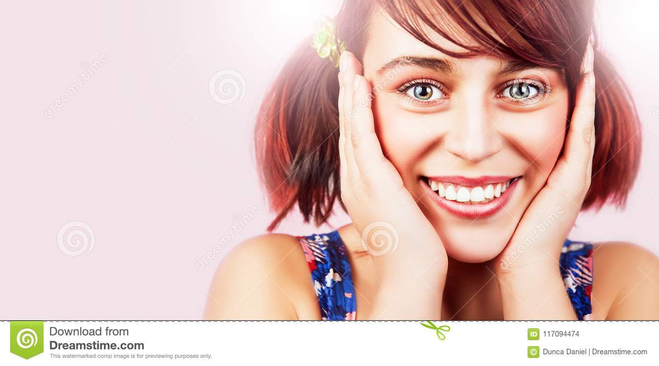 Face of friendly happy teen girl with natural cute smile over pink  background