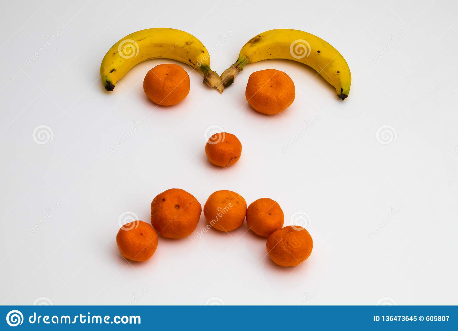 Face from fruits on white background. face made with fresh fruits. banana, mandarin tangerine