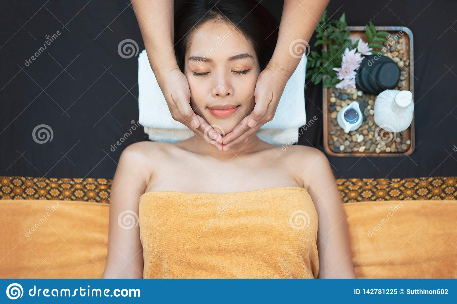 Face massage. Close-up of young woman getting spa massage treatment at beauty spa salon. Spa skin and body care. Facial beauty