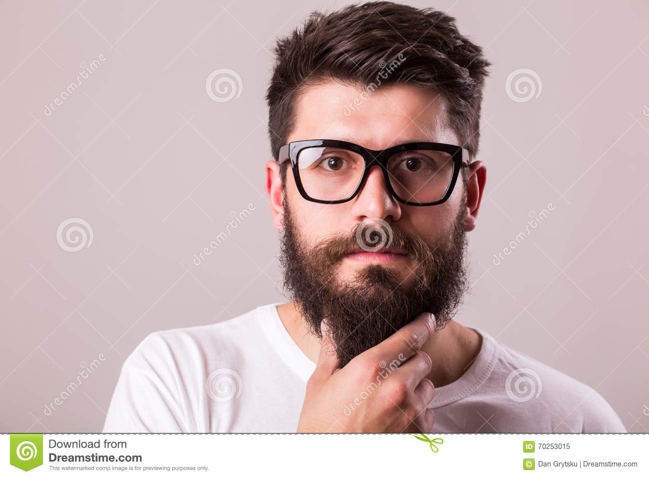 face portrait of bearded man in glasses with hand on beard stock