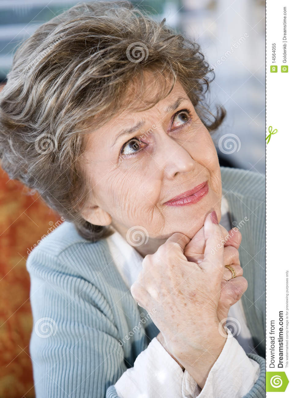 Face of serious elderly woman looking up