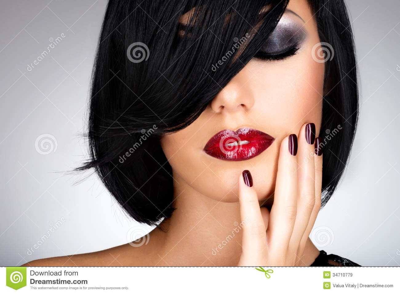 Face of a woman with beautiful dark nails and red lips