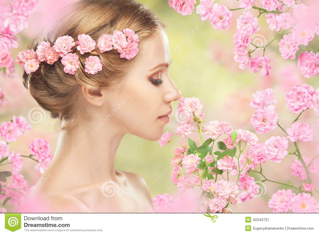 Face of young beautiful woman with pink flowers in her hair