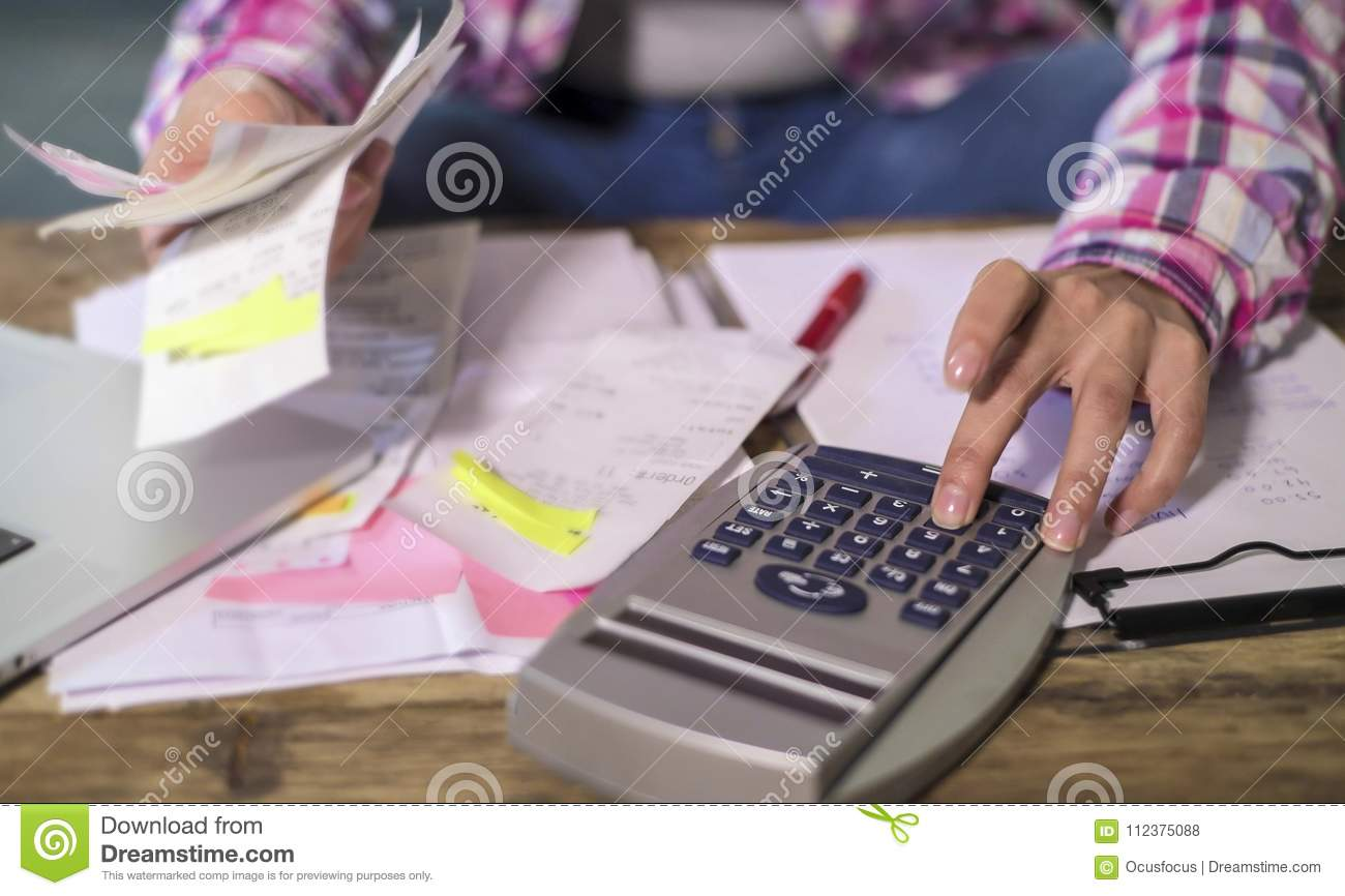 Faceless anonymous woman hands working with bank paperwork bills and financial documents calculating monthly expenses and debt wit