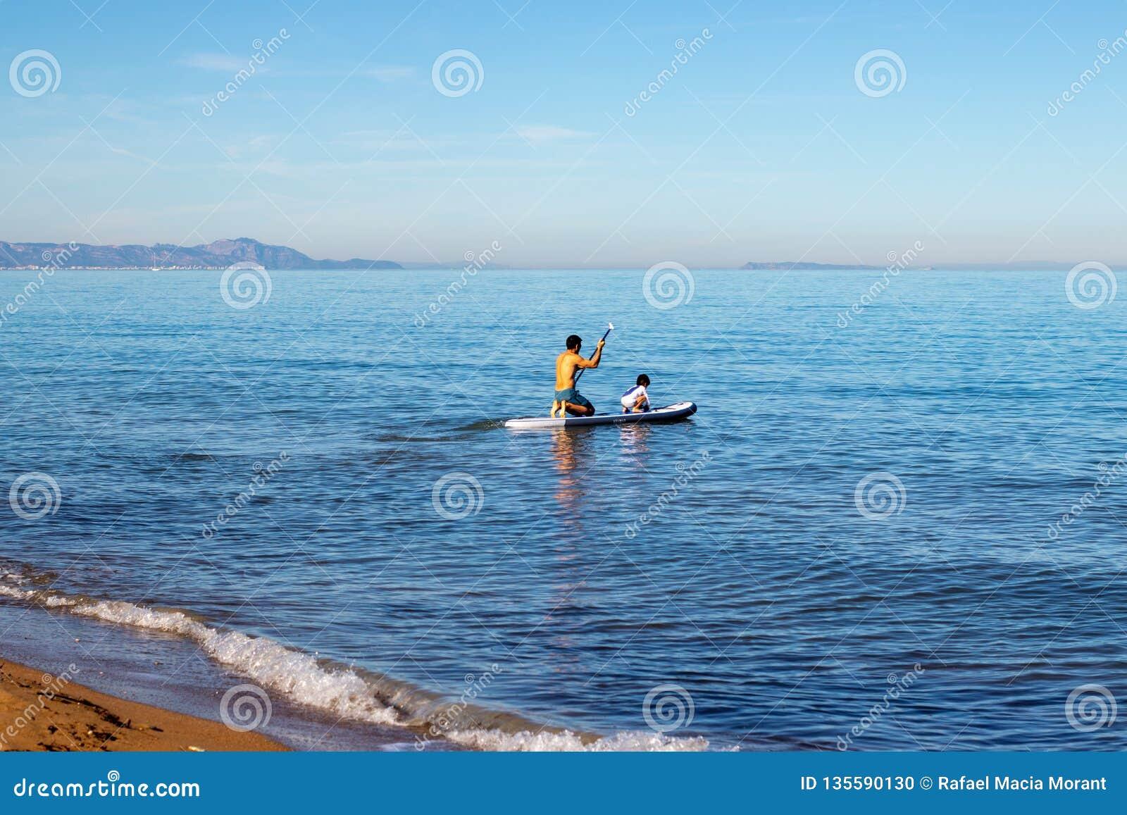 Facendo praticare il surfing della pagaia in famiglia con un piccolo bambino