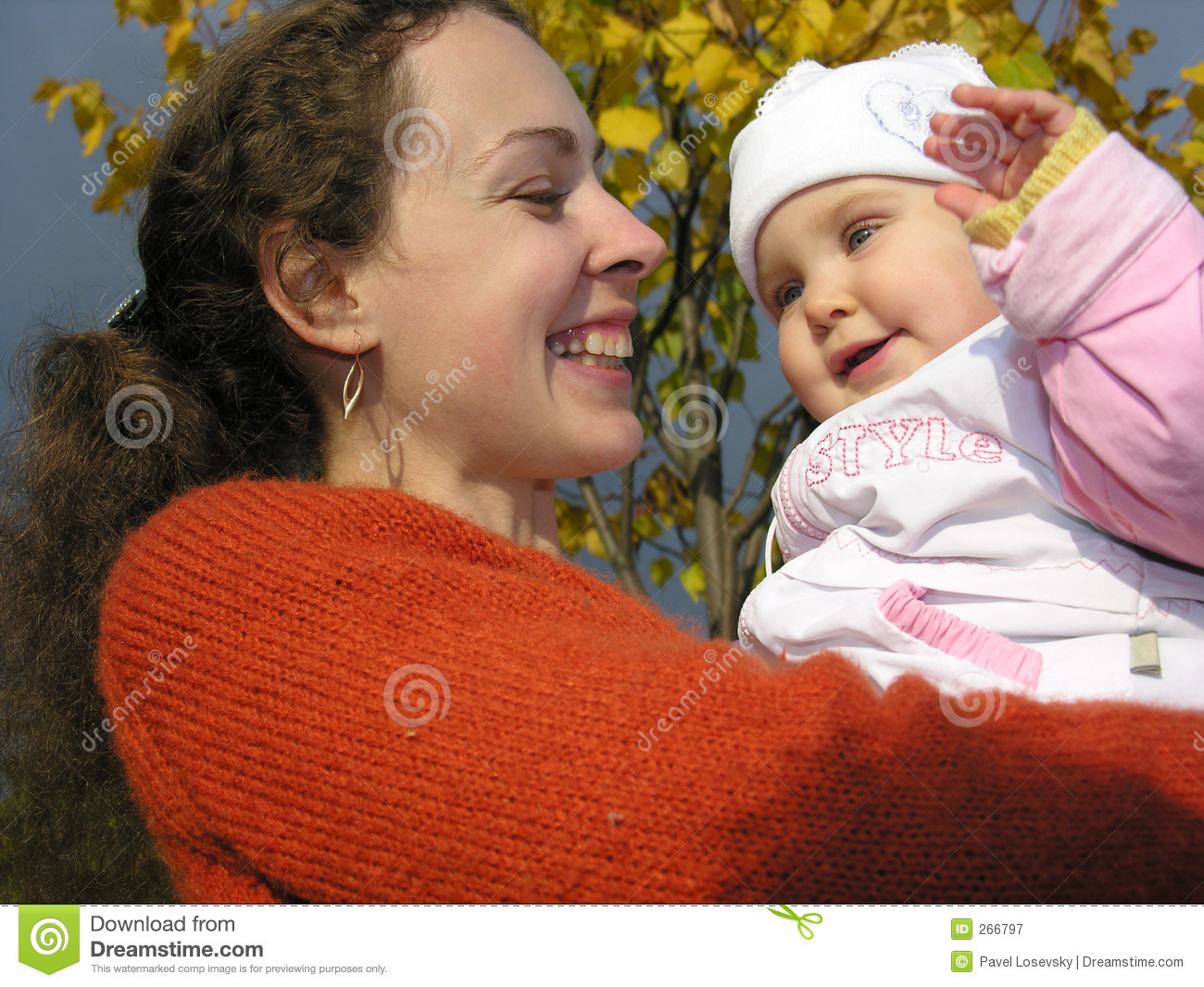 Faces mother with baby on autumn leaves
