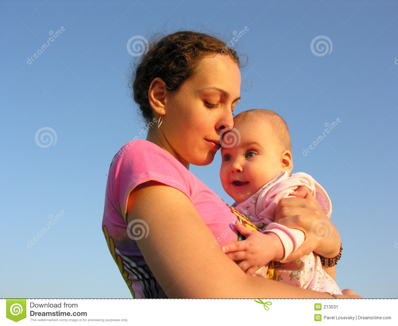 Faces mother with baby on sunset touch nose