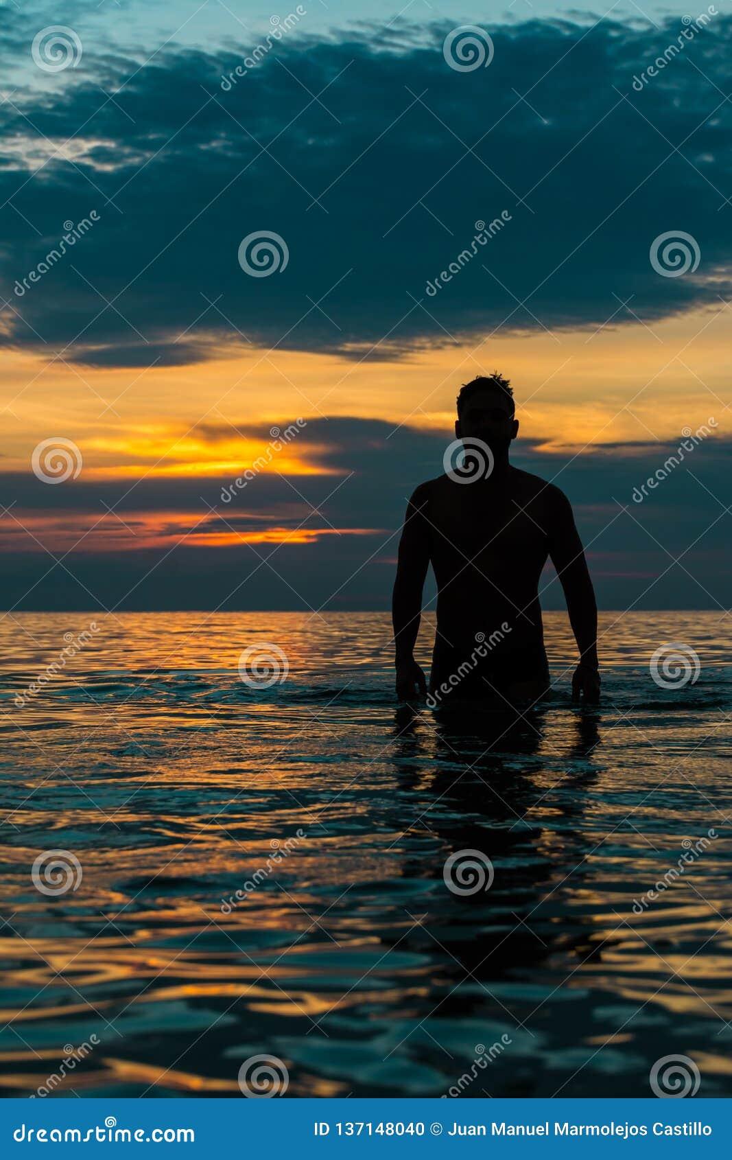 Facet chodzący za plaży od pod zmierzchem