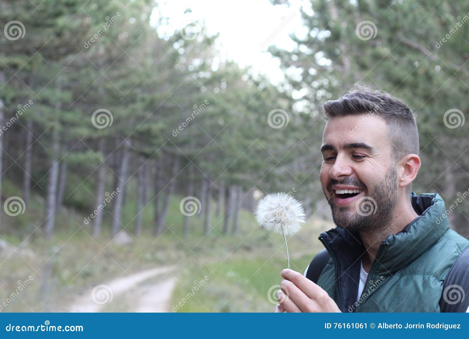 Facet ono uśmiecha się wokoło dmuchać na białym dandelion w lesie z kopii przestrzenią