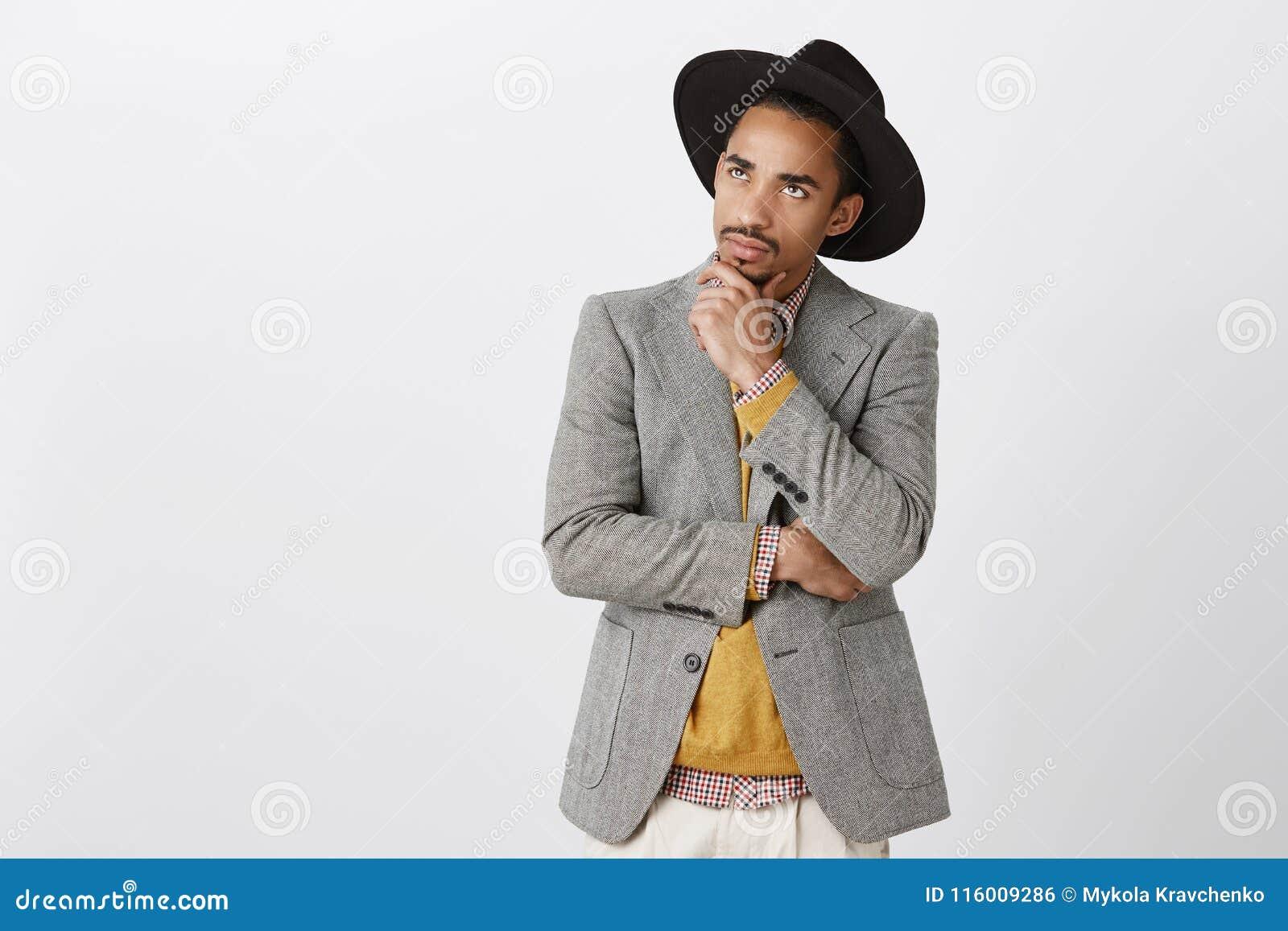 Facet skupiający się na myślach, robi trudnej decyzi Skoncentrowany poważny ciemnoskóry męski freelancer w czarnym kapeluszu i