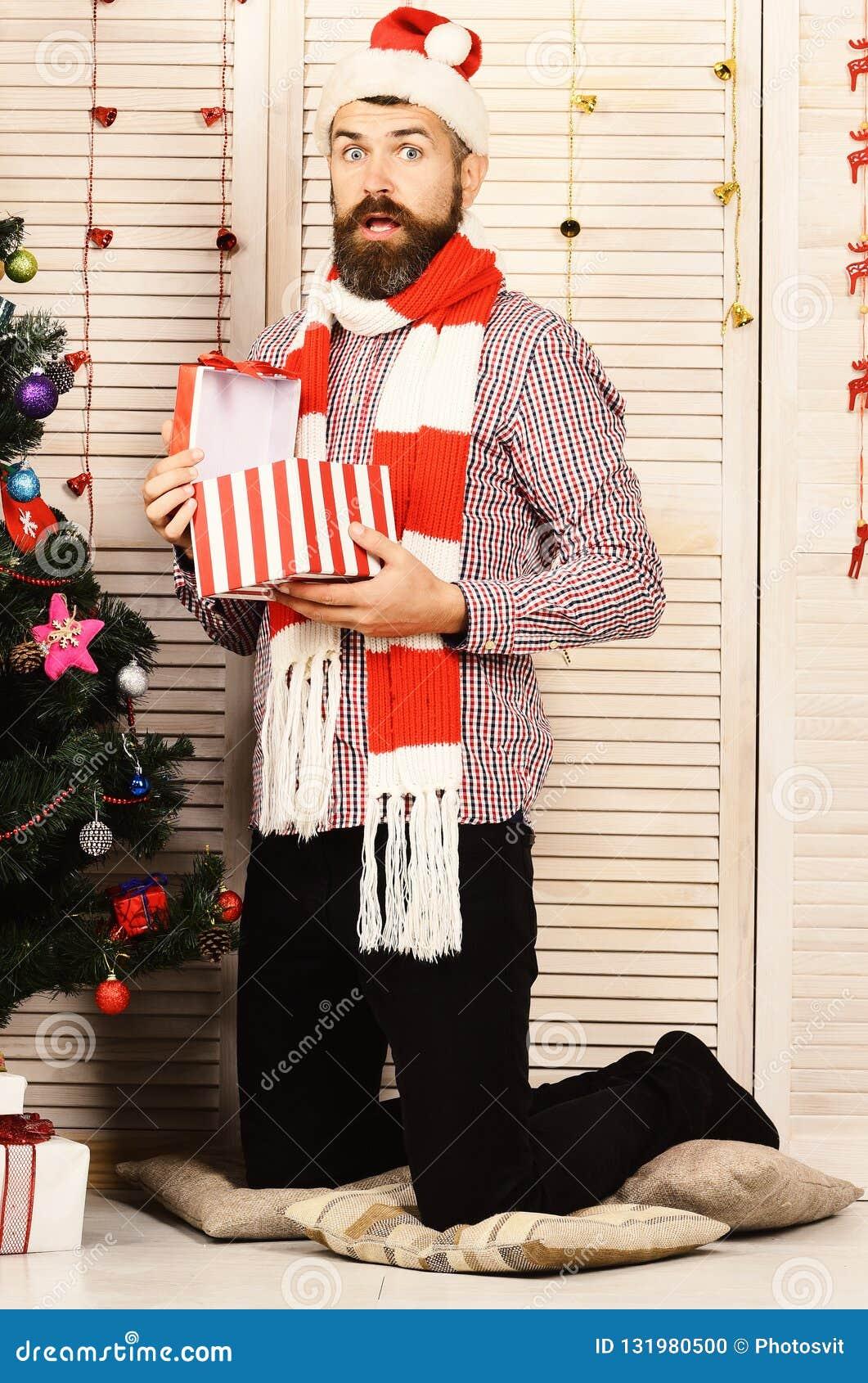 Facet stoi bezczynnie choinki Święty Mikołaj z zdziwioną twarzą
