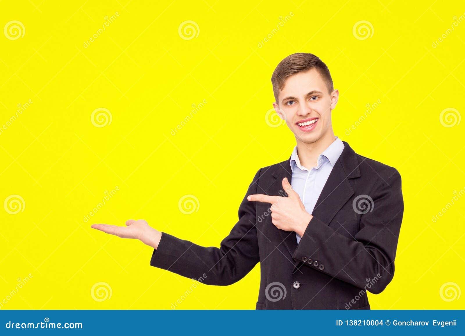 Facet w błękitnej koszula i kurtce reklamuje produkt odizolowywającego na żółtym tle