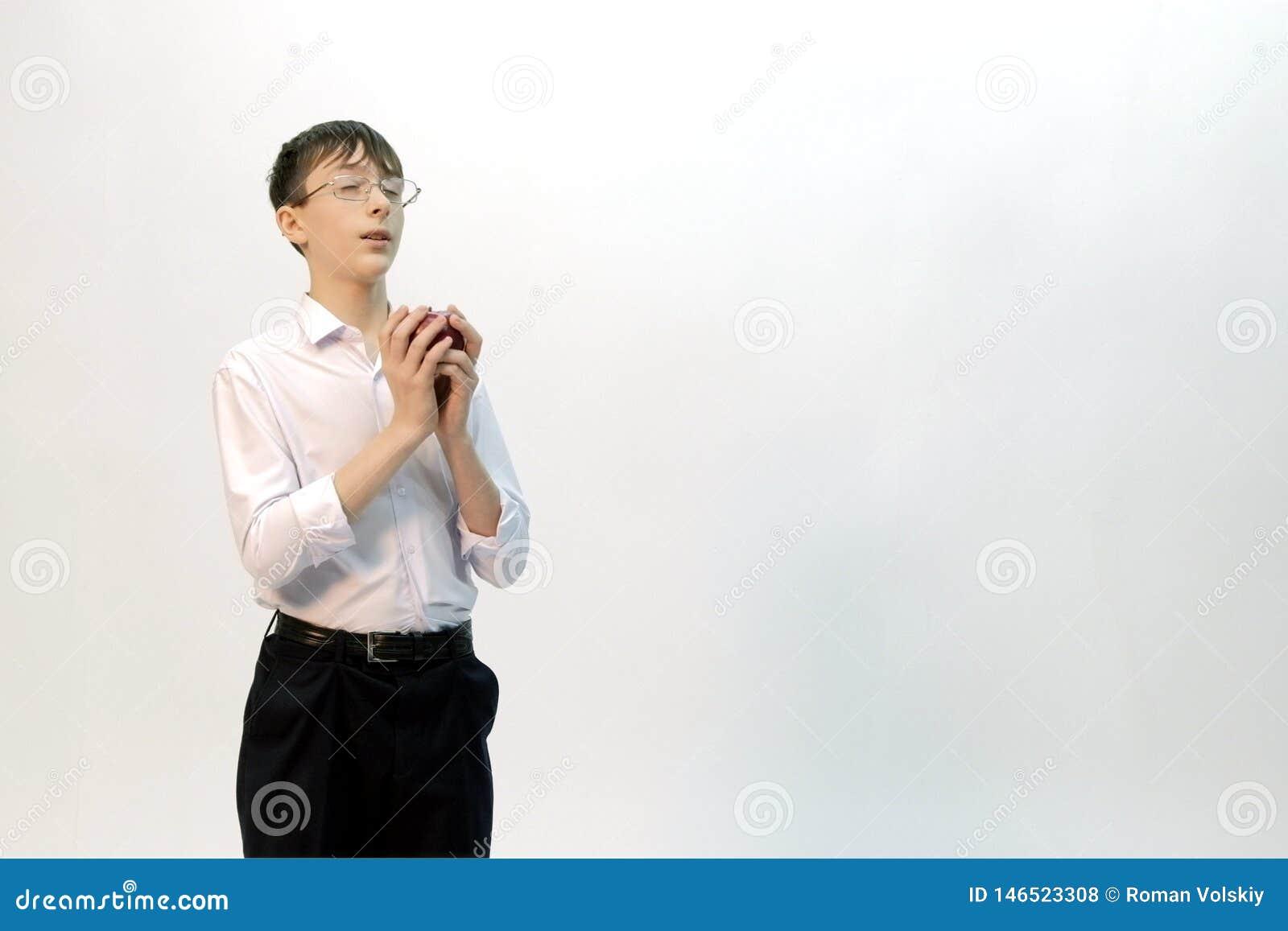 Facet z szkłami z jego oczami zamykającymi trzyma jabłka w jego rękach i marzy o coś Bia?y t?o kopia