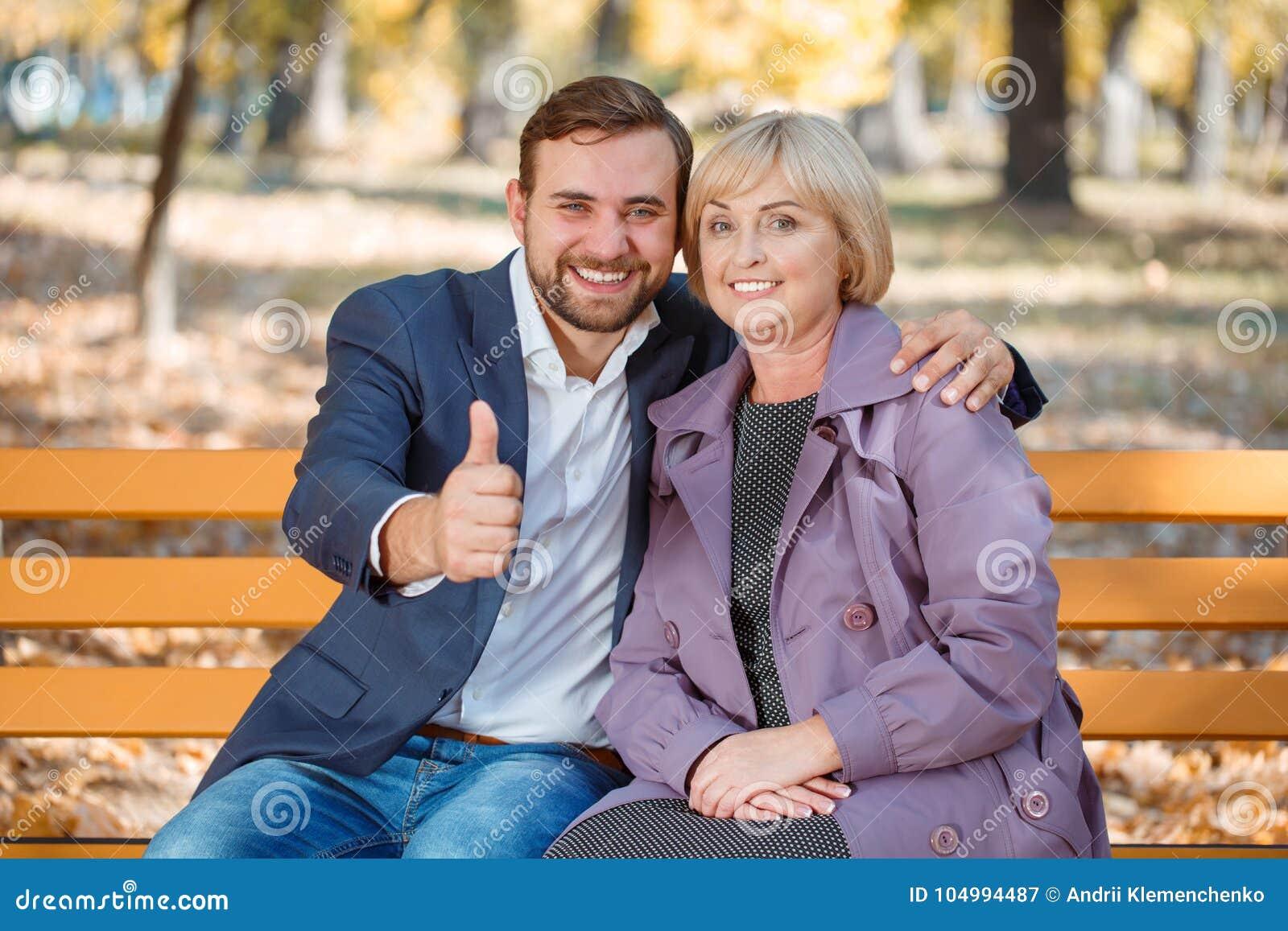 Facet z uśmiechem ściska mój matki w jesień parku na ławce
