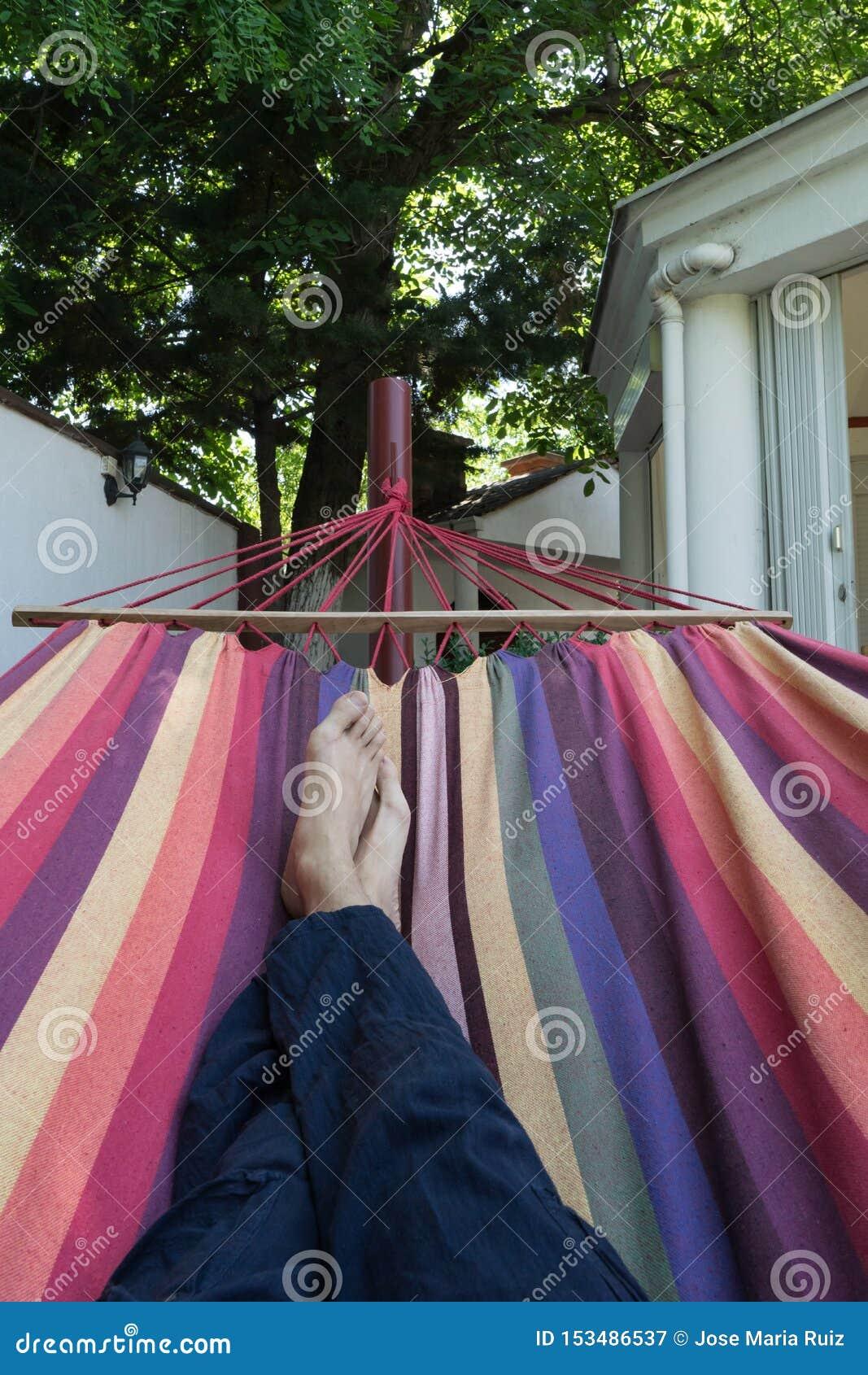Faceta łgarski puszek w kolorowy hamaka odpoczywać bosy Krzyżować nogi mężczyzna bierze drzemkę w błękitnych hipisów spodniach w