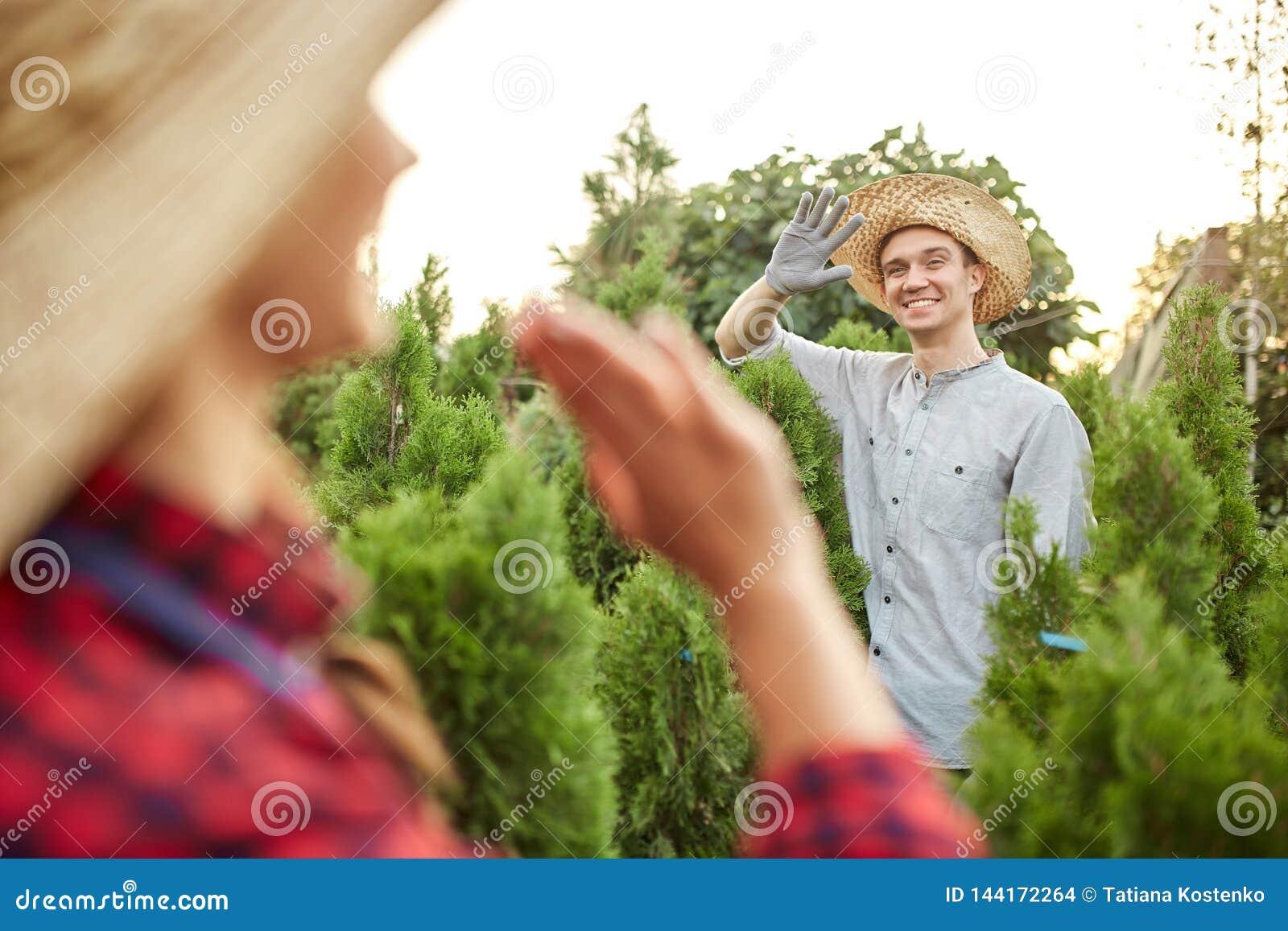 Faceta i dziewczyny ogrodniczki machają do siebie w ogródzie na ciepłym słonecznym dniu