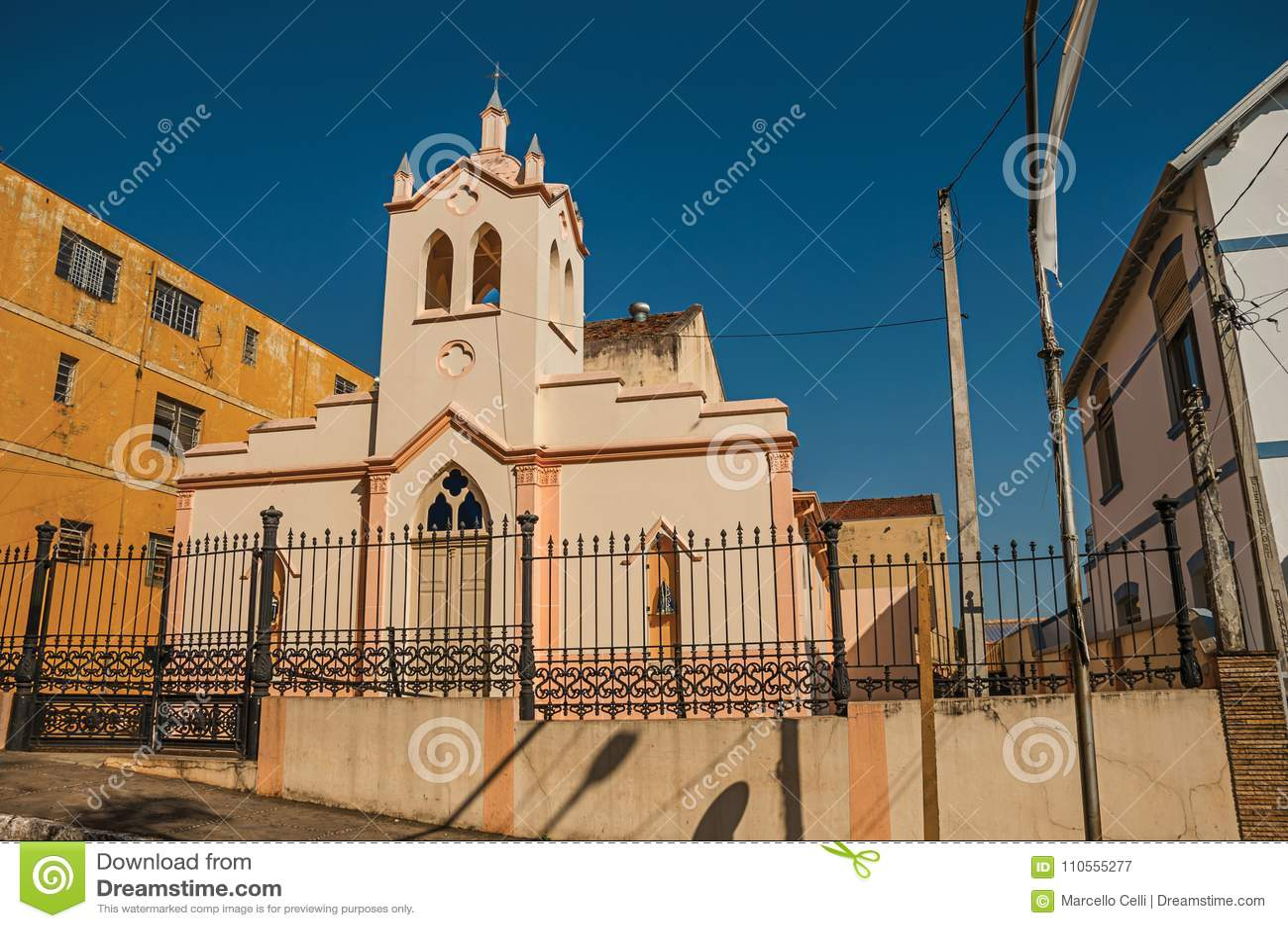 Fachada da igreja e da torre de sino pequenas atrás da cerca do ferro, em um dia ensolarado em São Manuel