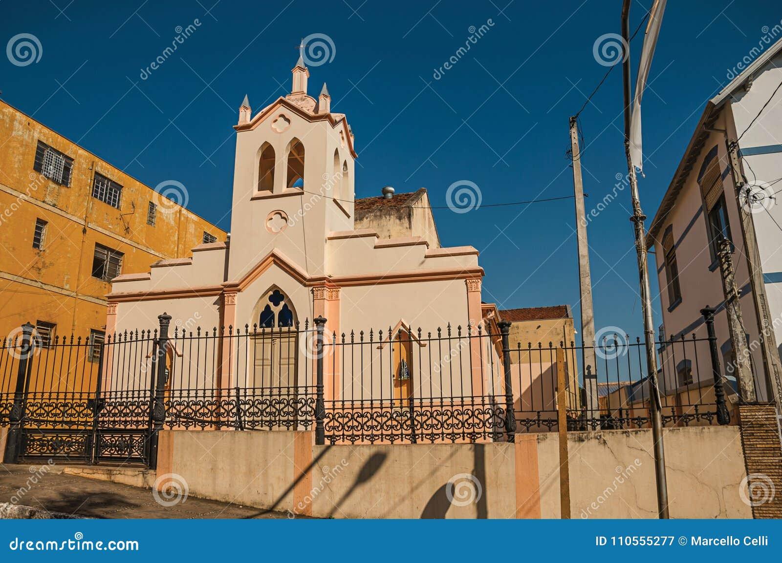 Fachada de la pequeños iglesia y campanario detrás de la cerca del hierro, en un día soleado en São Manuel