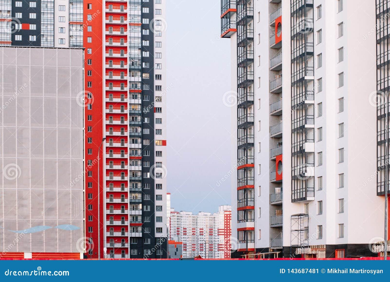 A fachada de um prédio com as listras brancas e cinzentas vermelhas construção do Multi-andar contra o céu azul Fundo a