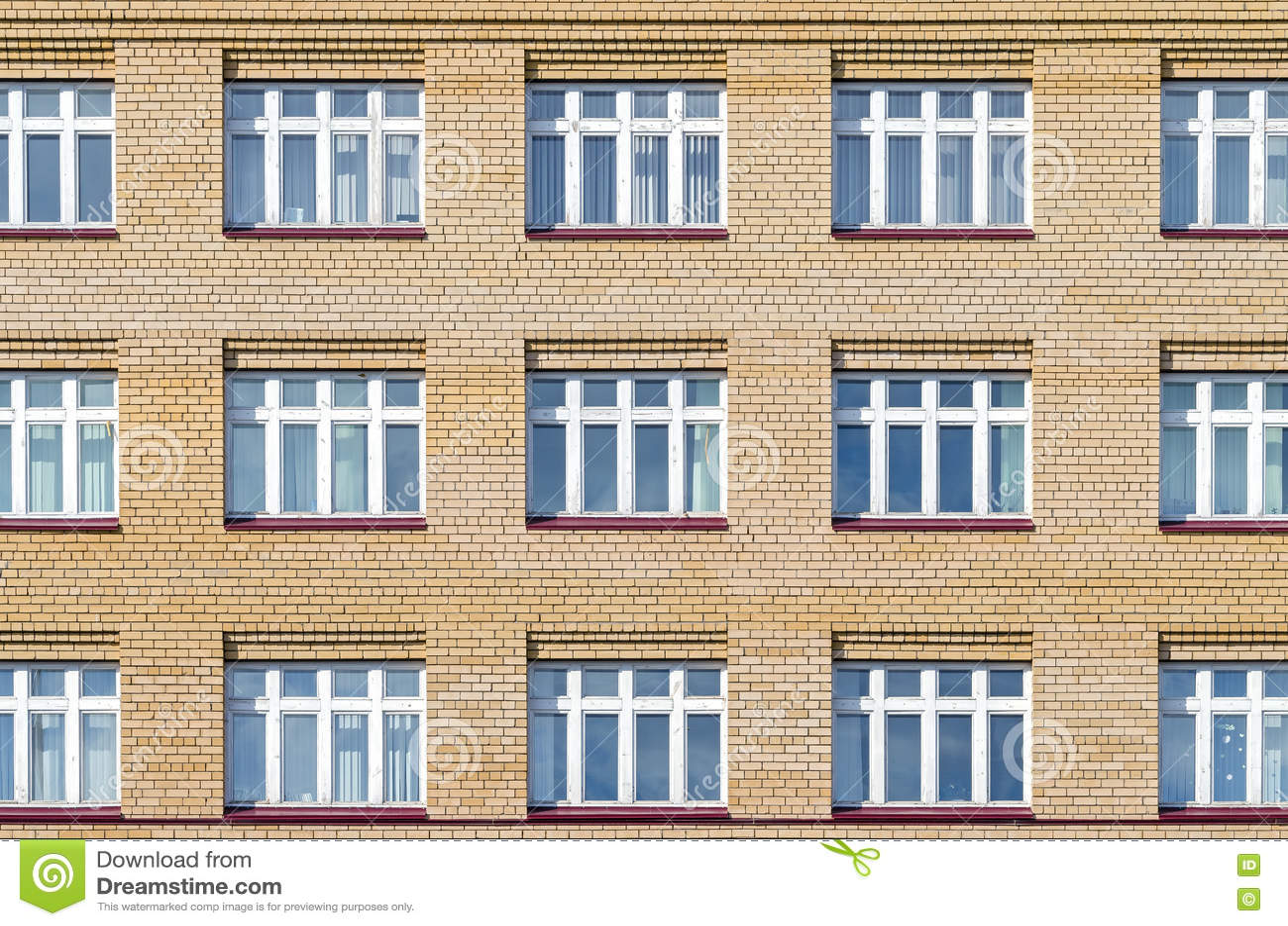 fachada del ladrillo de la casa con las ventanas blancas