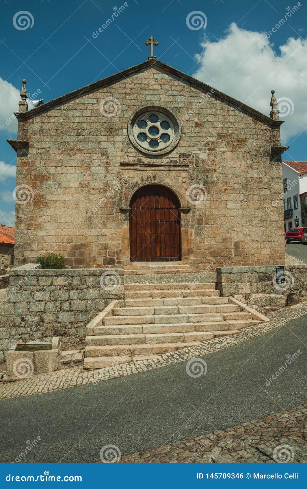 Fachada medieval da igreja com a parede de pedra em Monsanto