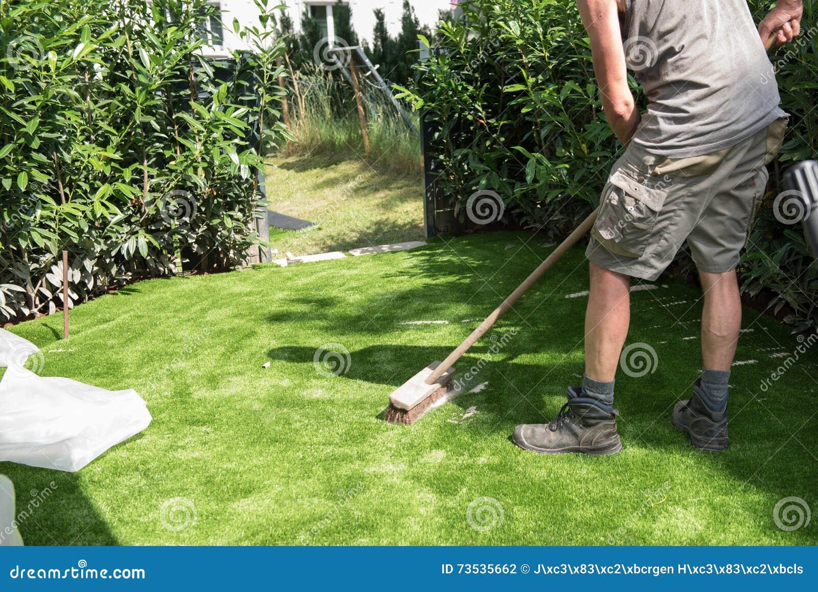 Fachowa ogrodniczka stawia piasek na sztucznej murawie