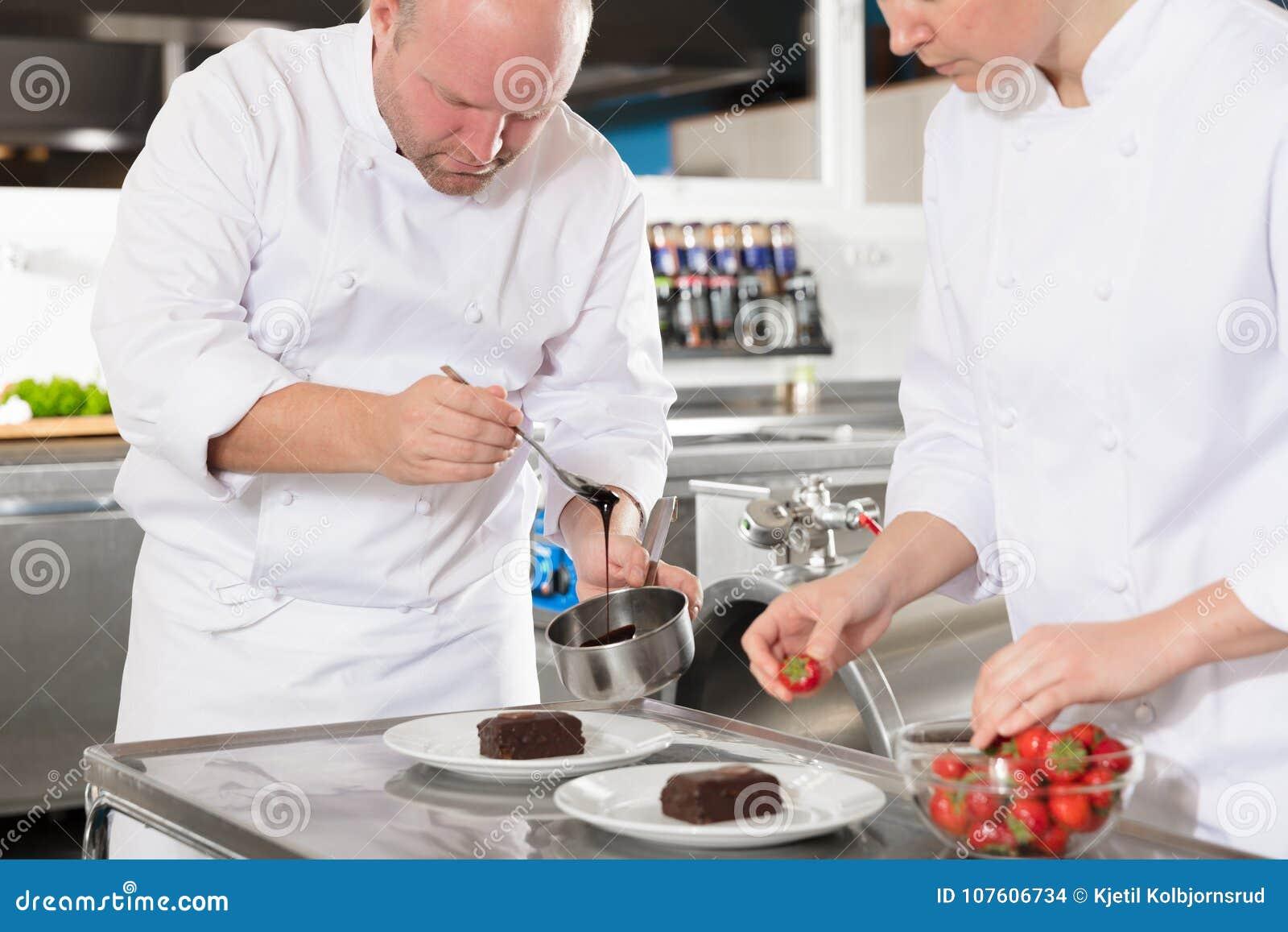 Fachowi szefowie kuchni dekorują deseru tort z cytryna liściem