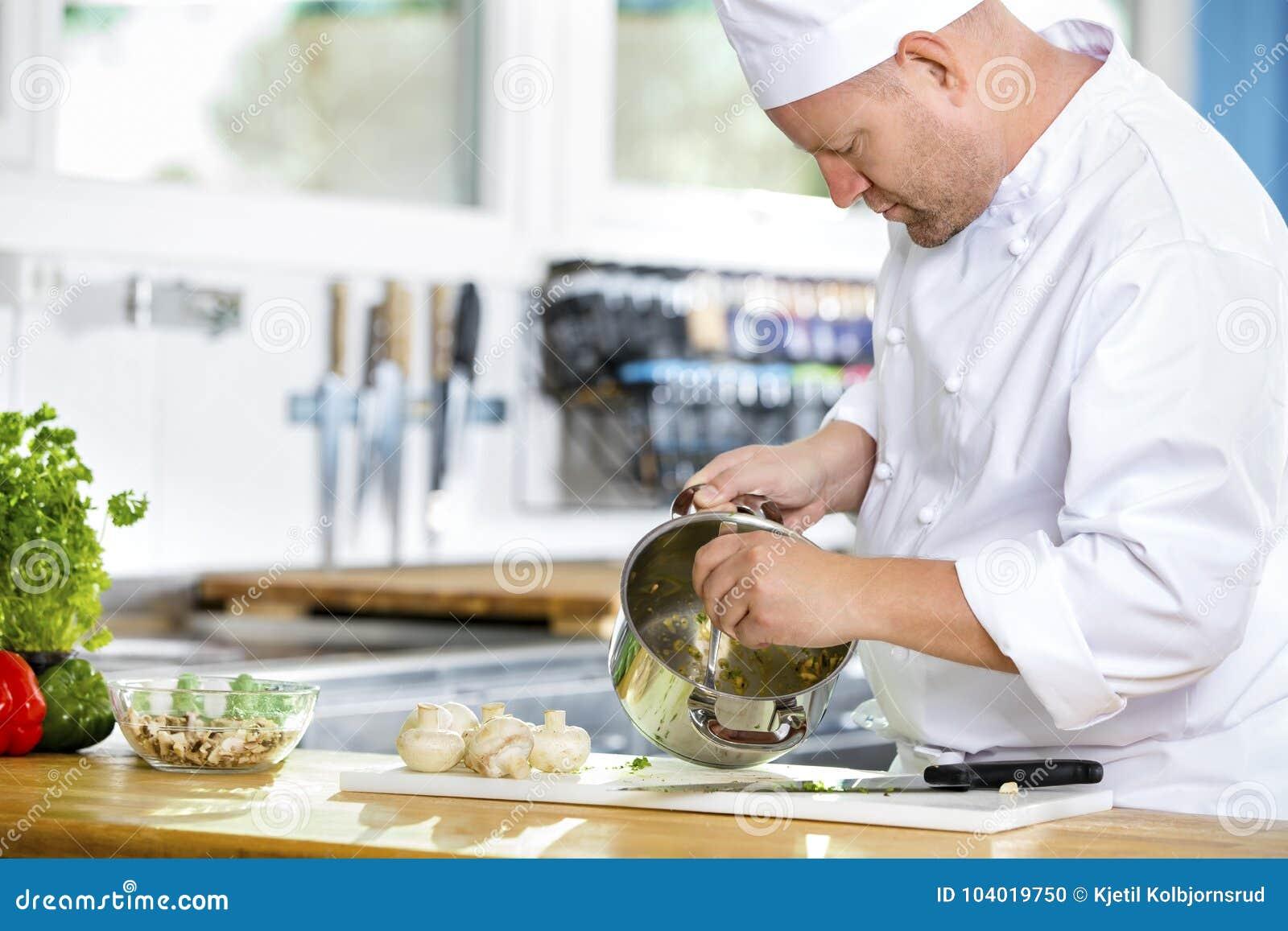 Fachowi szefowie kuchni robią karmowym naczyniom w wielkiej kuchni
