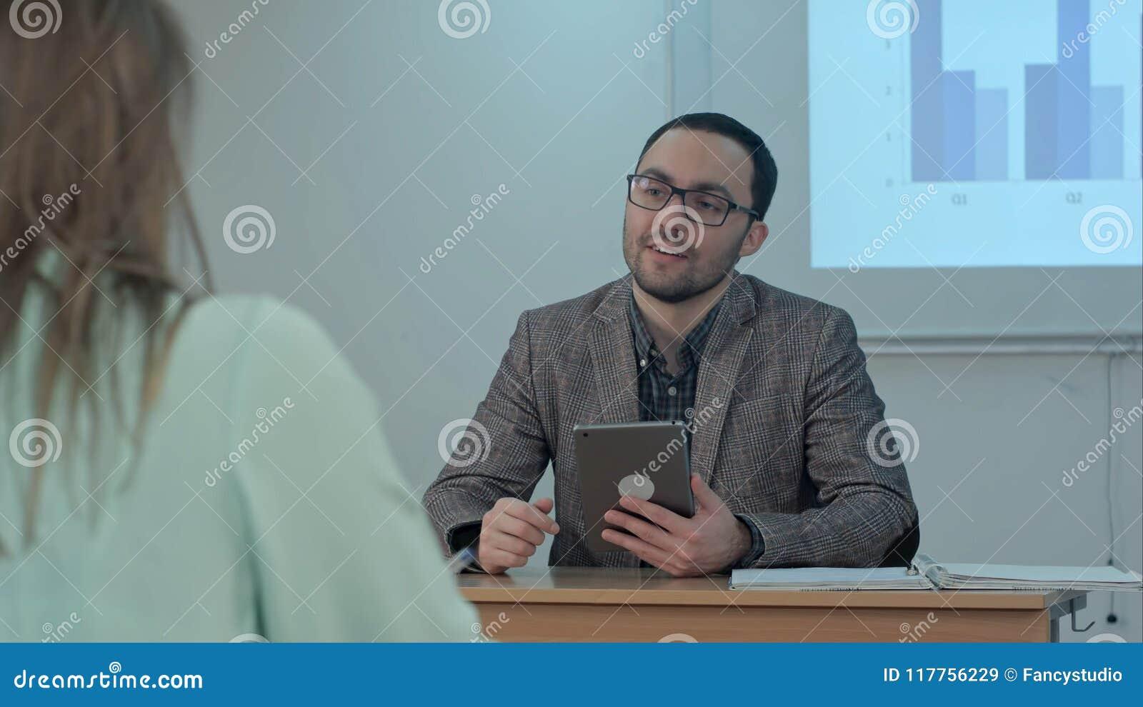 Fachowy męski nauczyciel wyjaśnia głównych pomysły robi dyskusi między uczniami pyta pytania i dzielić esej