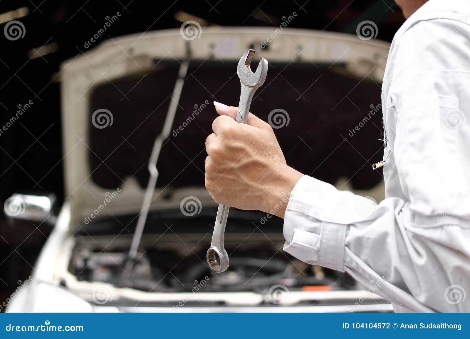 Fachowy młody mechanika mężczyzna w jednolitym mienia wyrwaniu z otwartym kapiszonem przy remontowym garażem tła samochodowy poję
