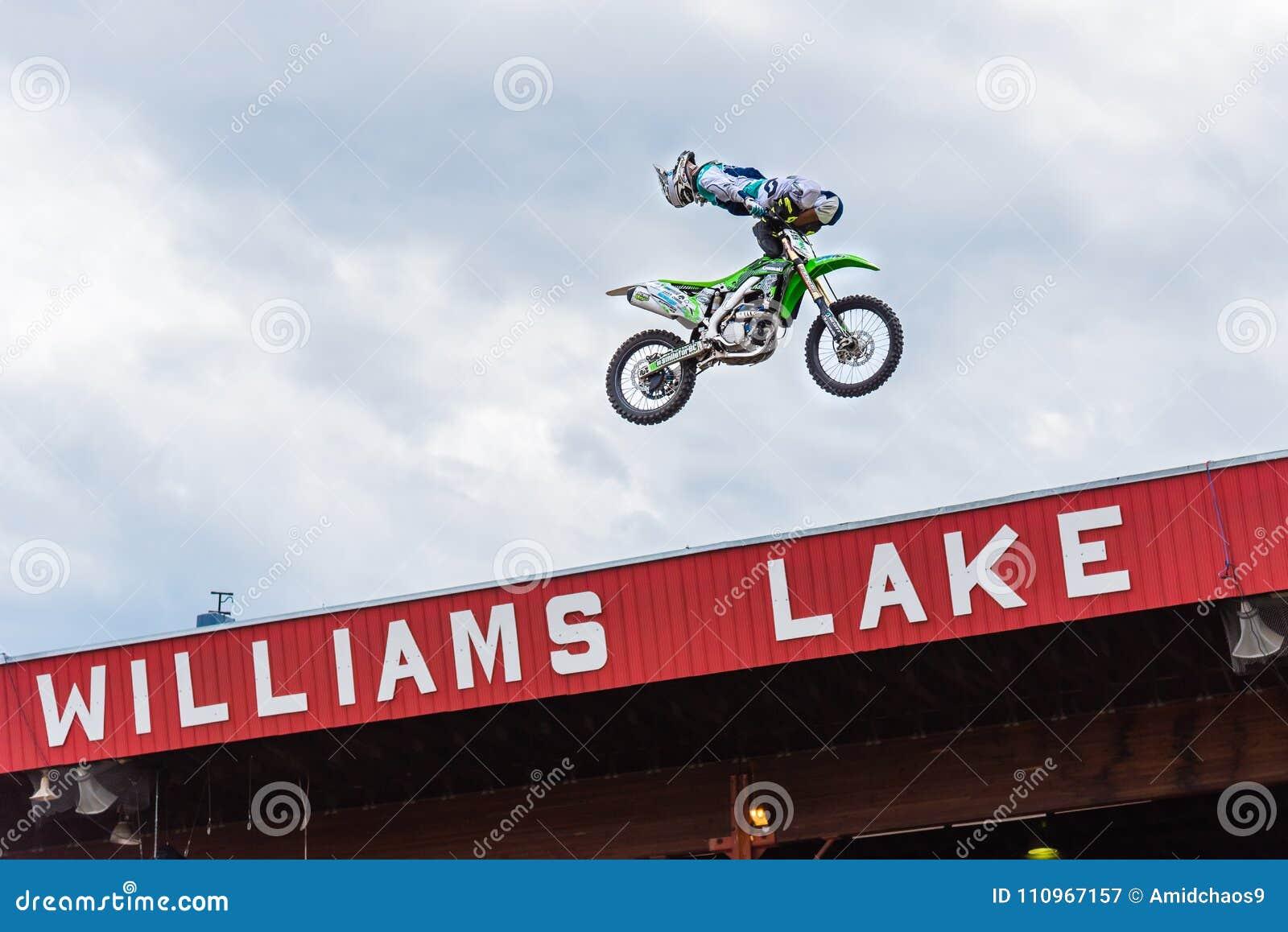 Fachowy stylu wolnego motocross członek zaspołu wykonuje wyczyn kaskaderski wysokość nad widownia