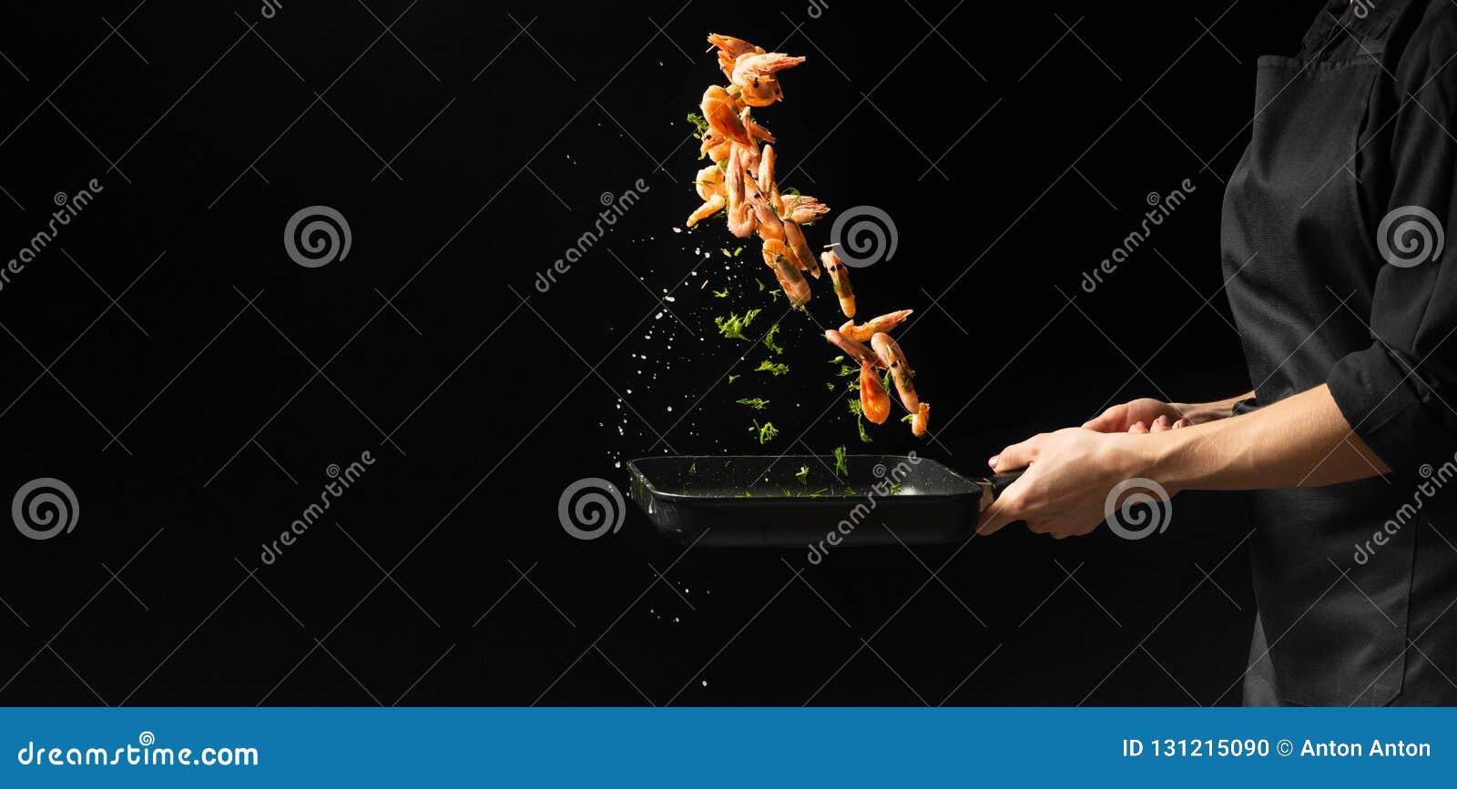 Fachowy szef kuchni przygotowywa garnele z zieleniami Kulinarny owoce morza, zdrowy jarski jedzenie i jedzenie na ciemnym tle, ho