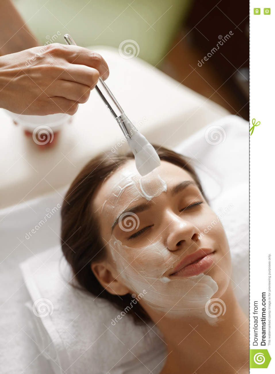 Facial Beauty Treatment. Beautiful Woman Getting Cosmetic Mask