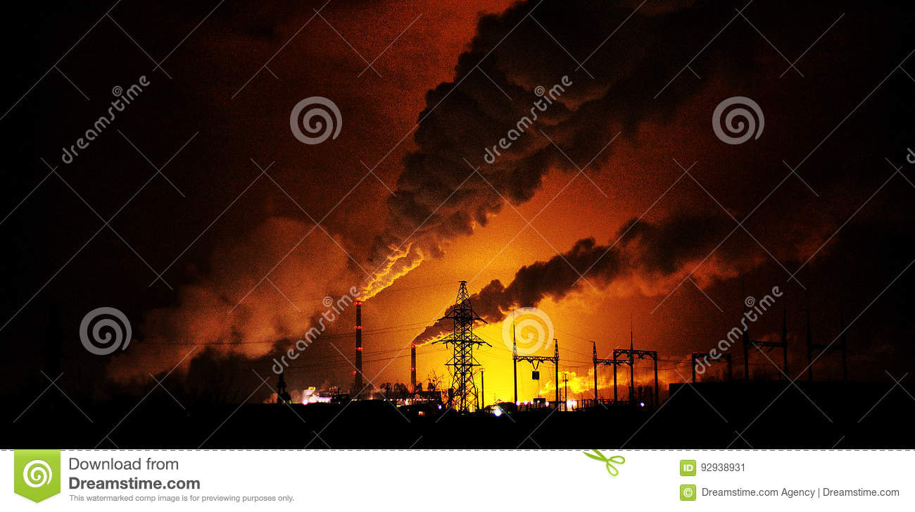 Factories at night, the silhouettes of the pipe producing a noxious smoke