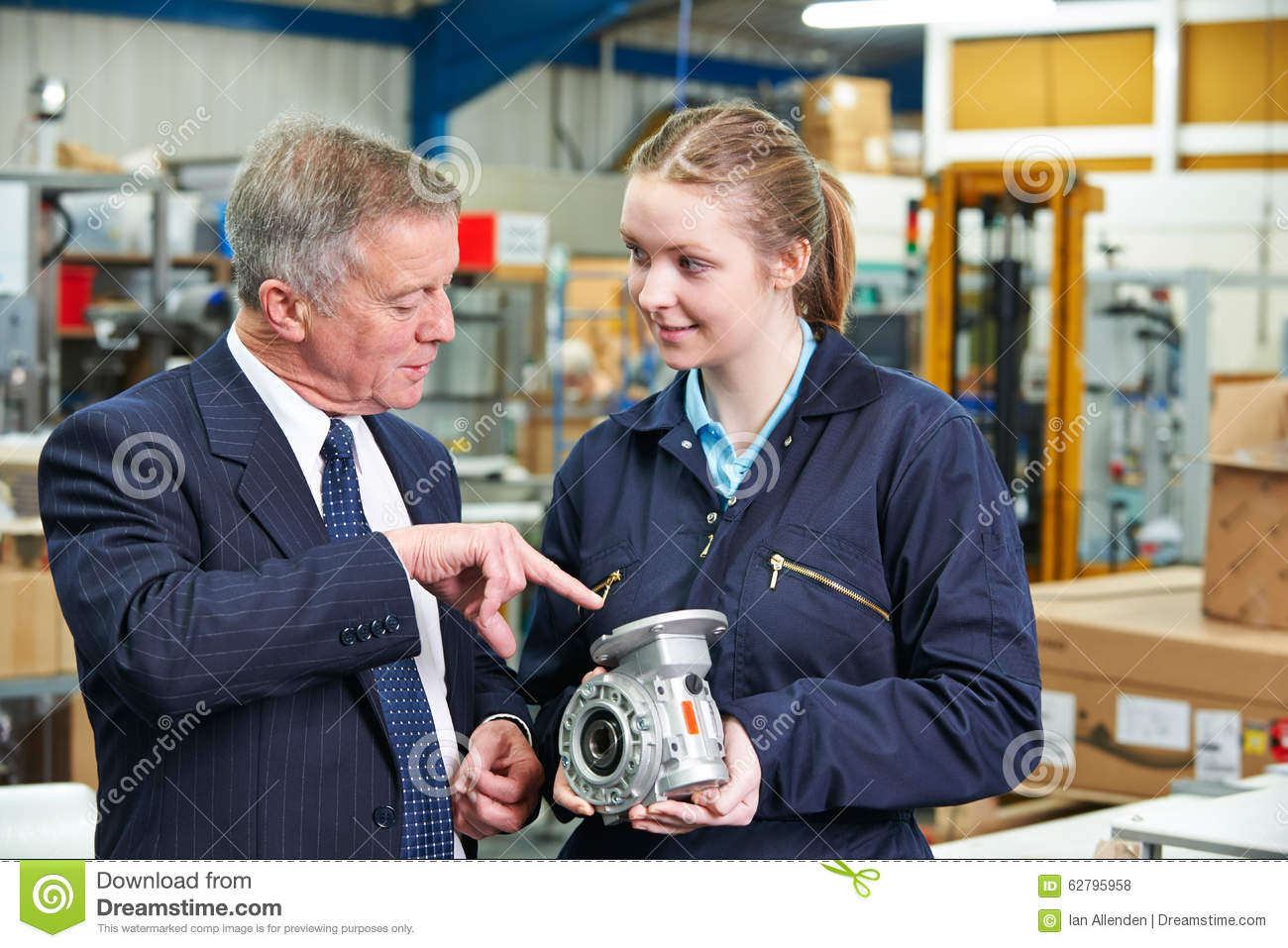 Factory Manager And Engineering Apprentice Discussing Component