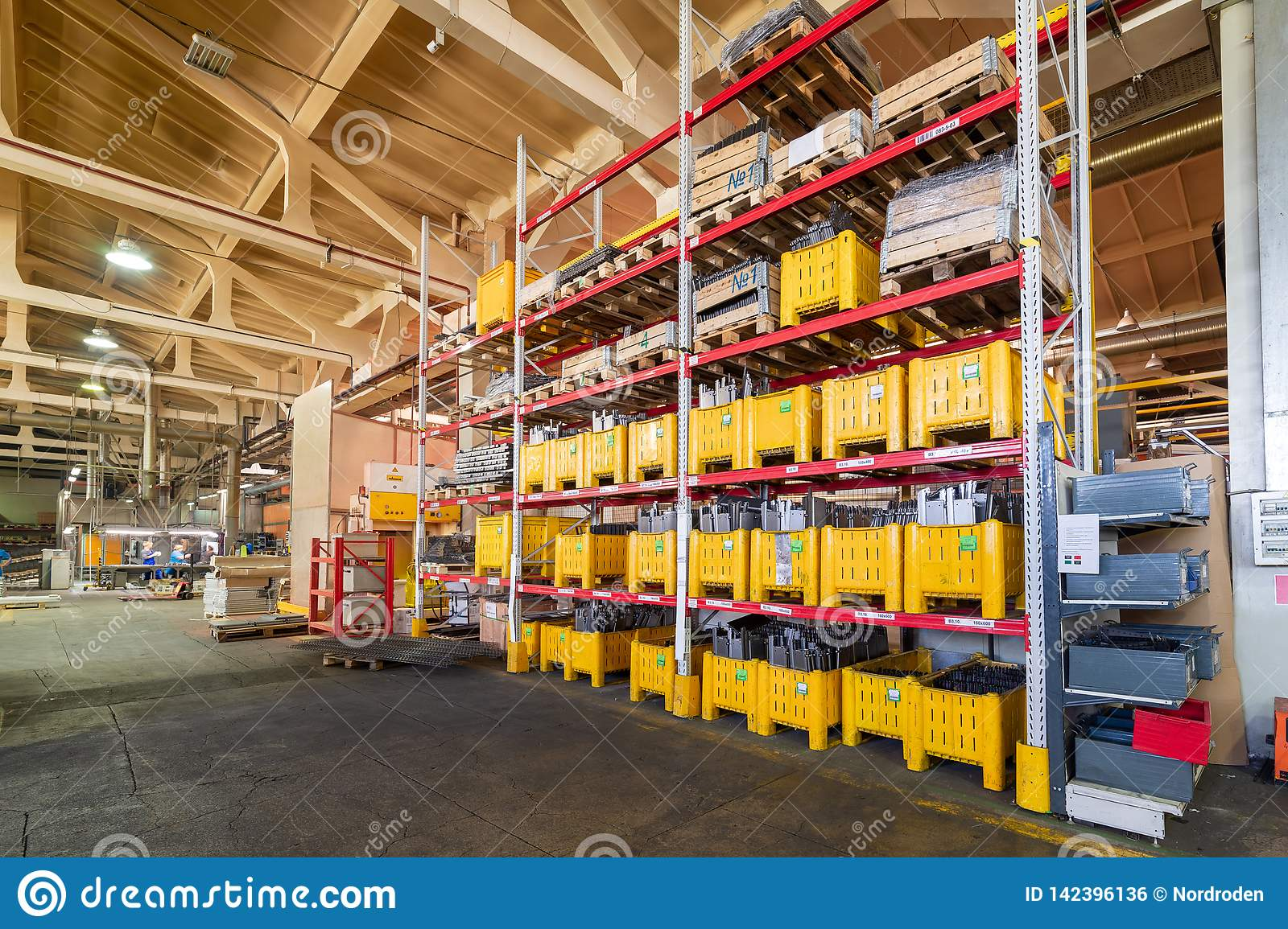 Factory warehouse steel reinforcement. large yellow plastic boxes on the shelves.