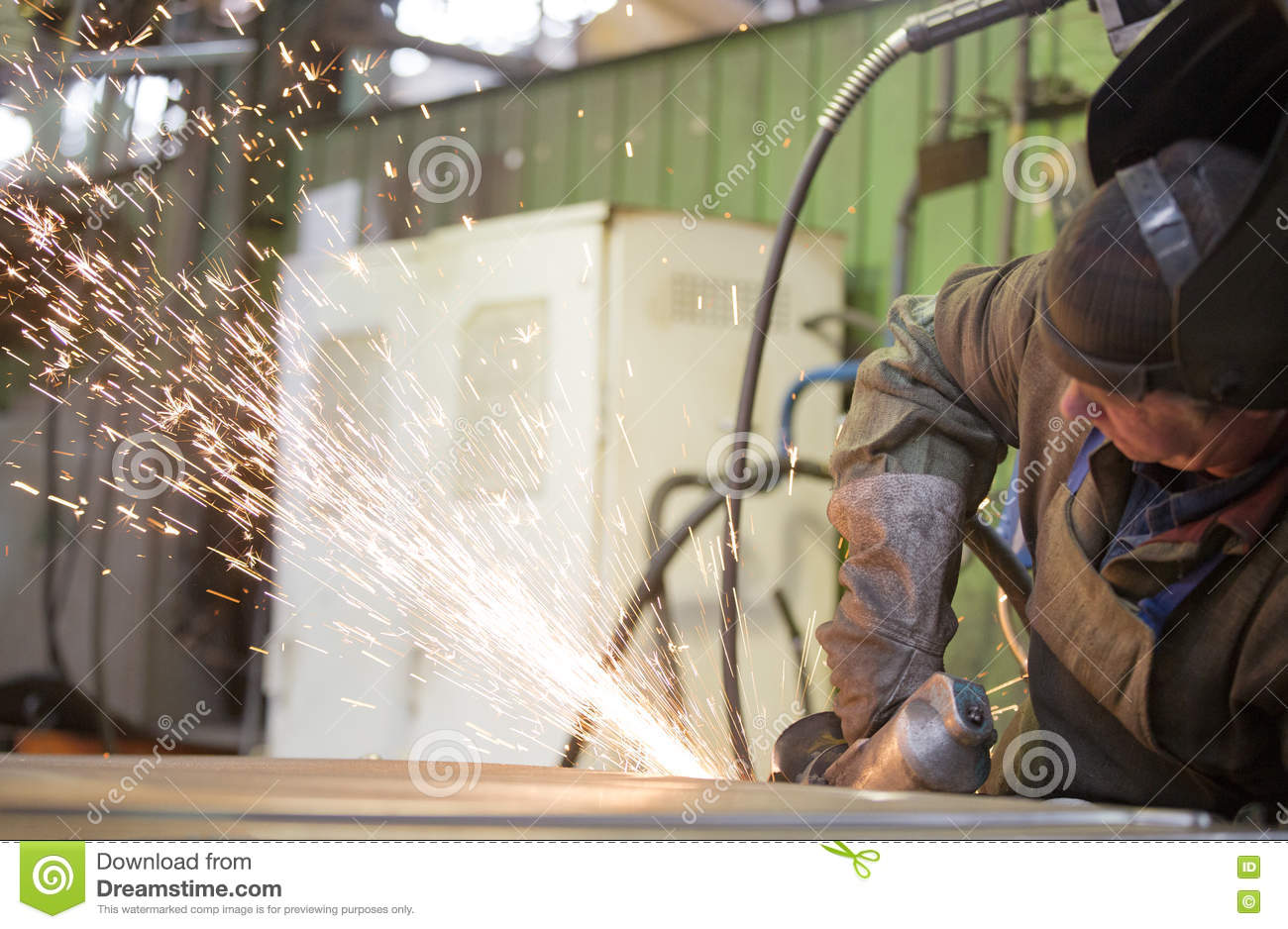 Factory Worker Grinding Steel Sheet With Flying Sparks