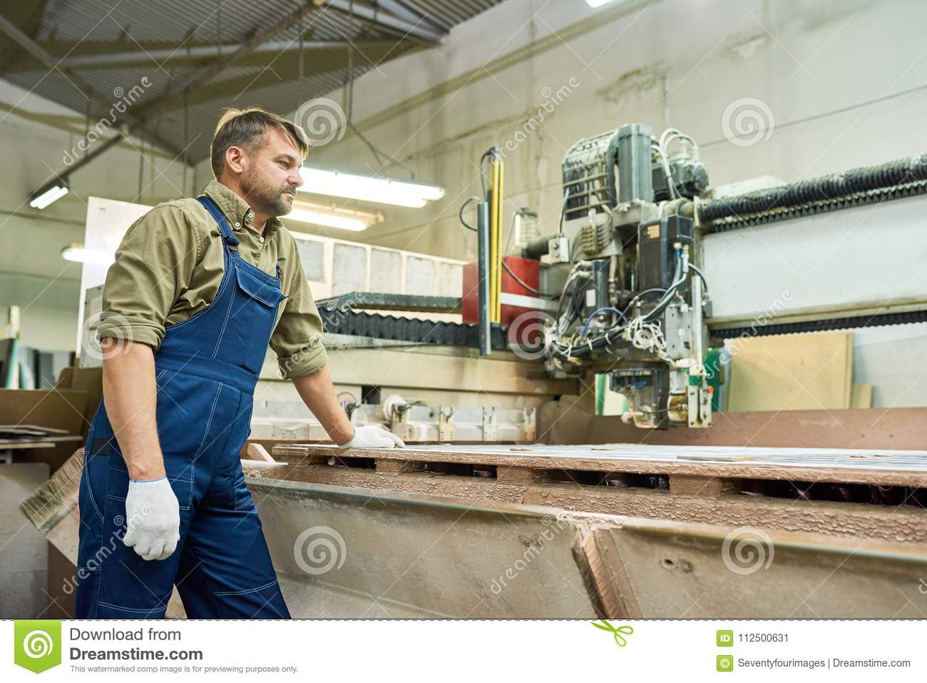 Side view portrait of mature workman standing by wood cutting machine in modern furniture factory copy space