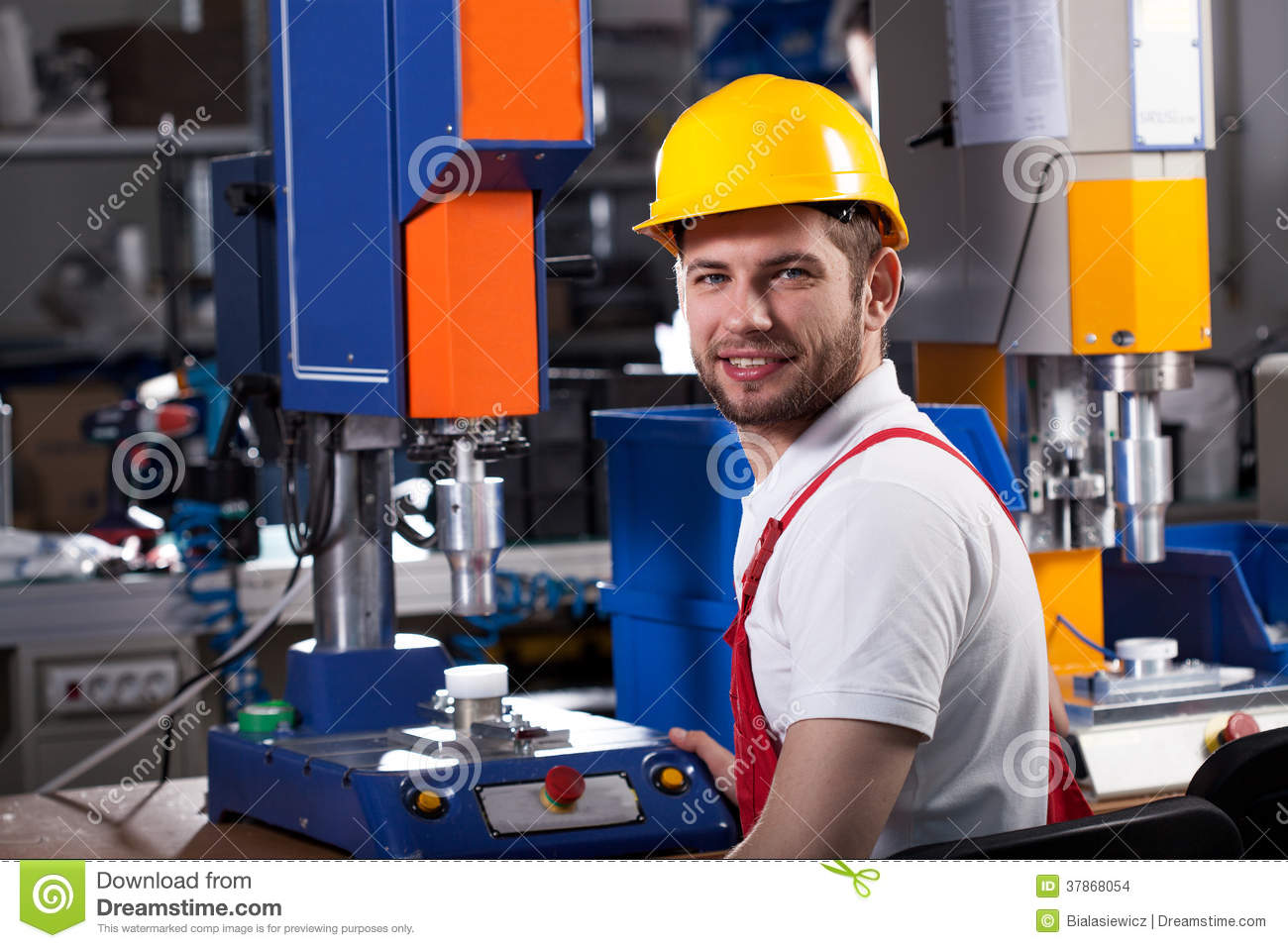 Young handsome factory worker in yellow helmet during work.