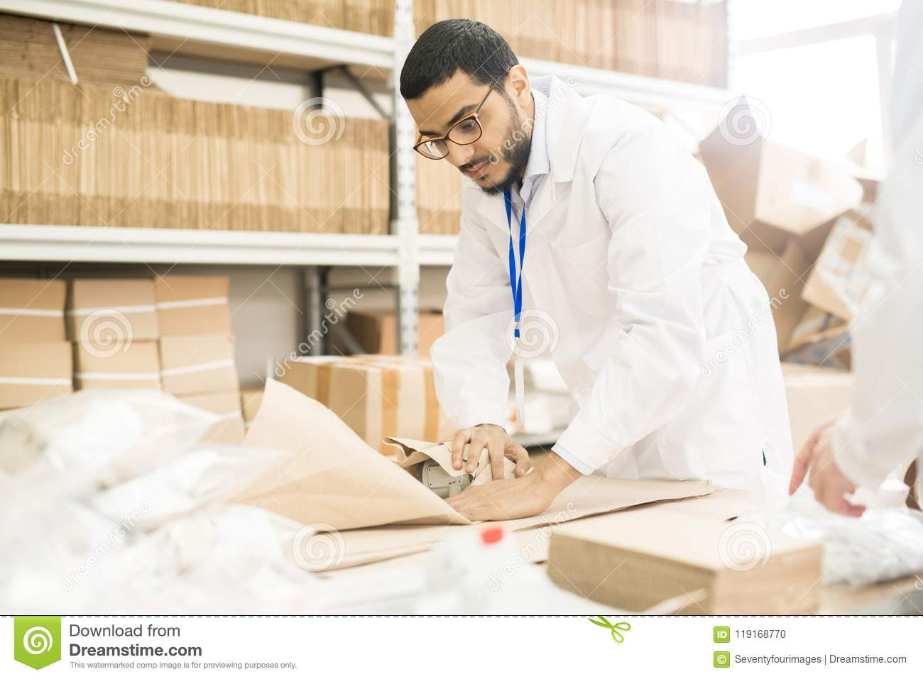 Factory Worker Wrapping Manometer in Paper