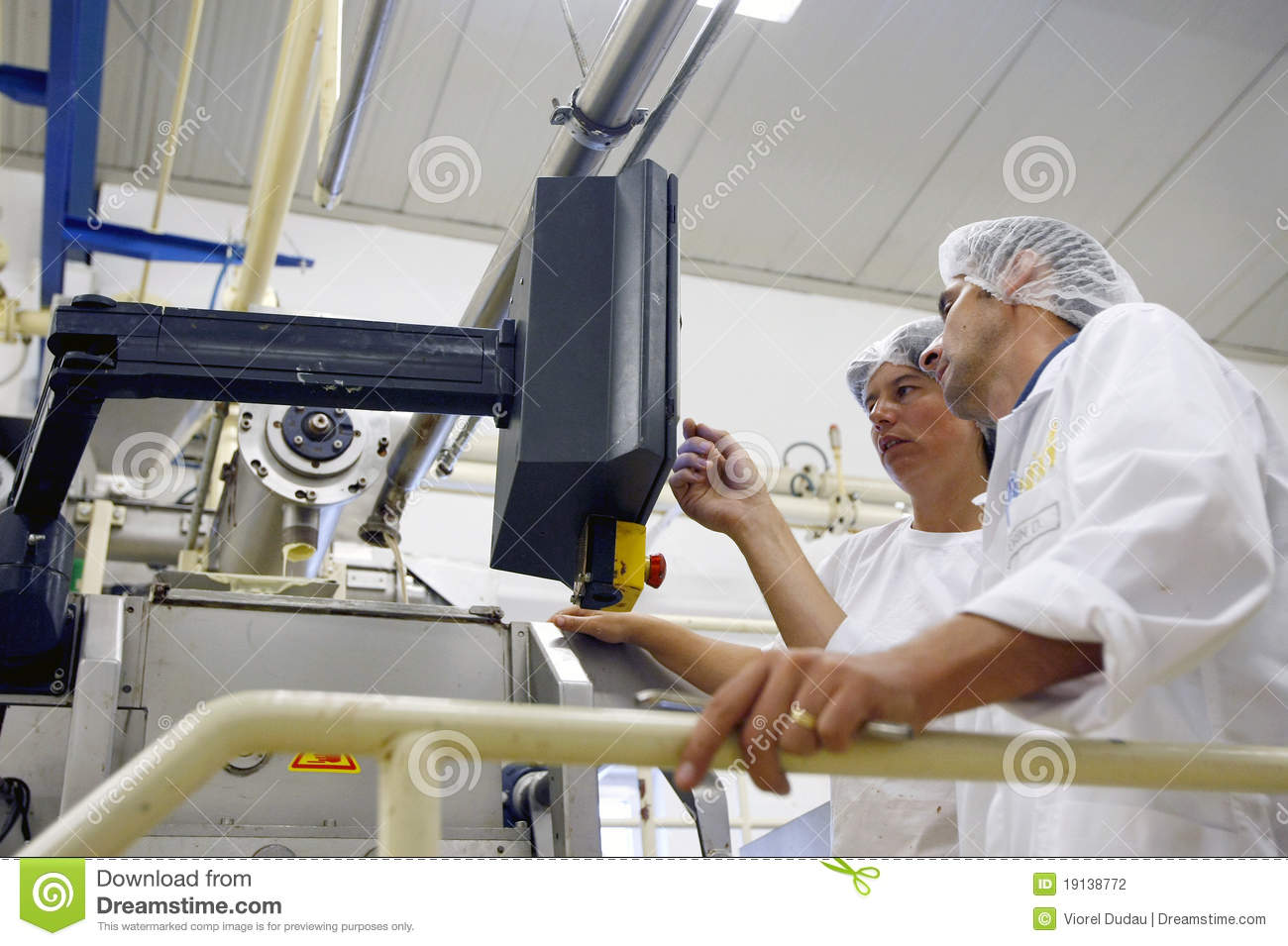 Factory workers operating the control panel