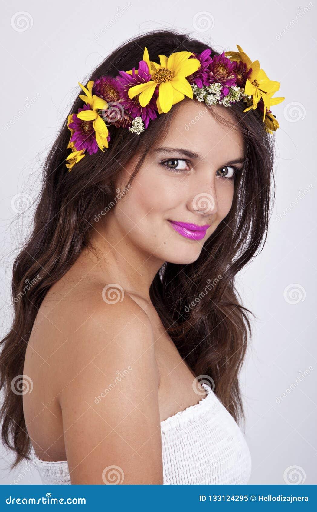 A fada bonita, feliz está sorrindo, na grinalda vestindo da flor do vestido branco Fotografia artística, retrato